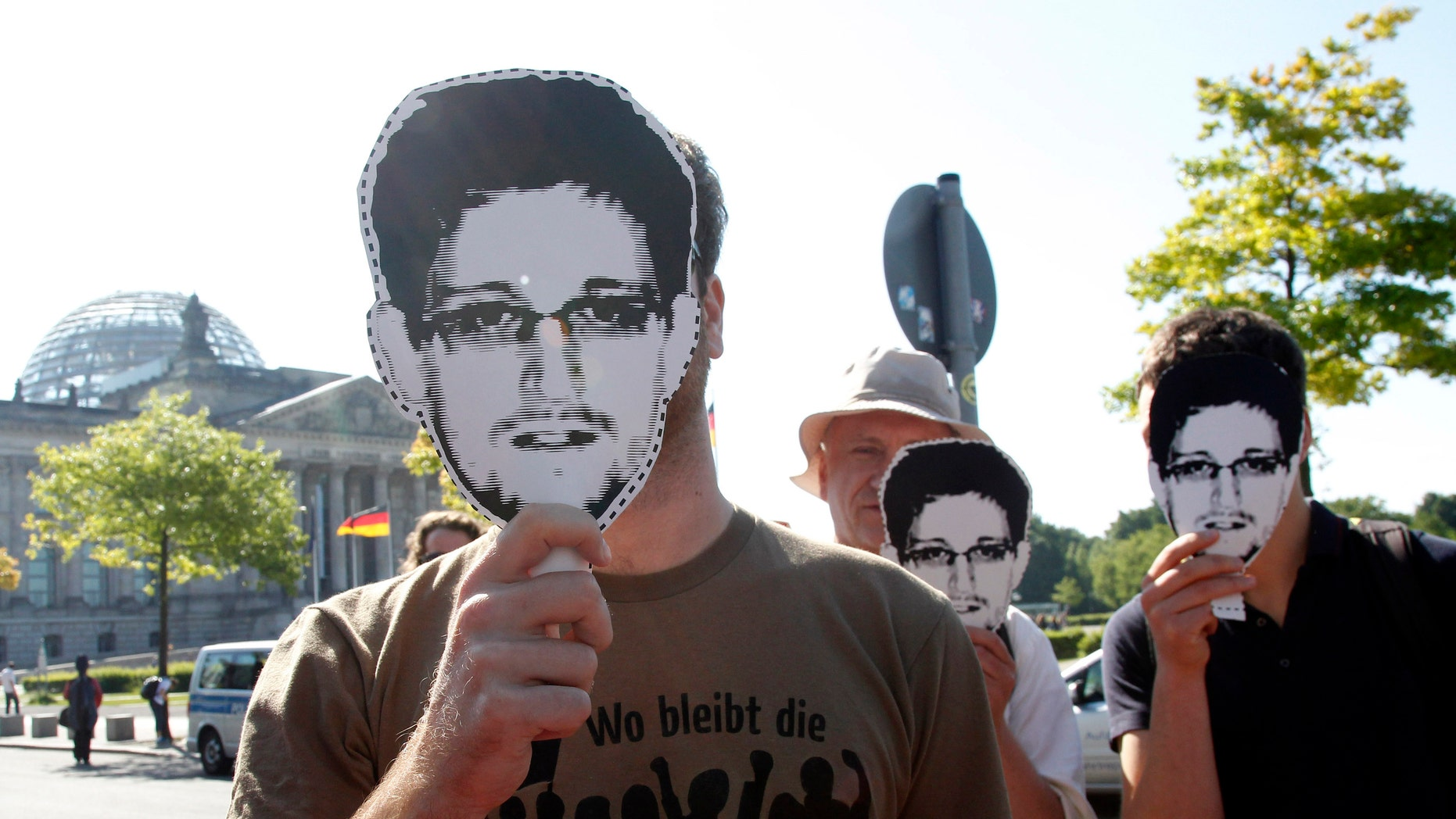 Protesters hold masks depicting former U.S. National Security Agency contractor Edward Snowden during a demonstration in Berlin May 22, 2014.