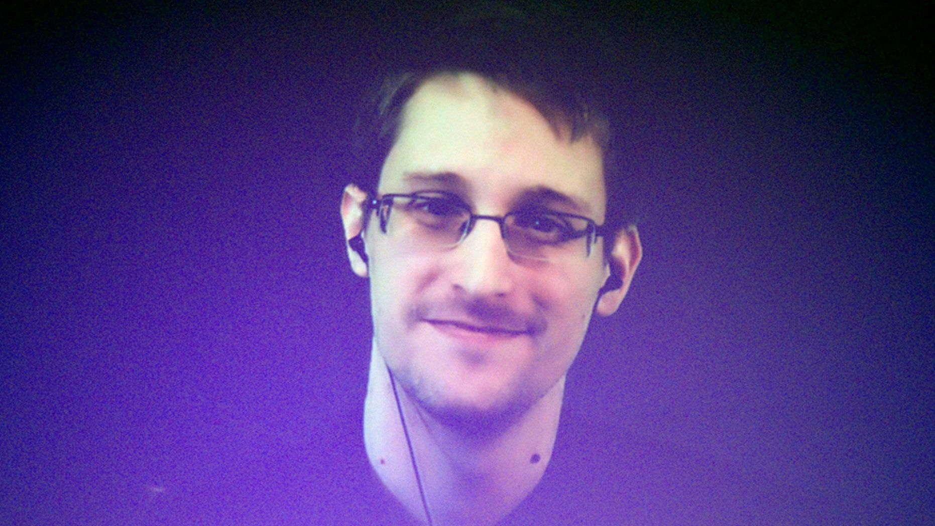 Edward Snowden, who is in Moscow, is seen on a giant screen during a live video conference for an interview as part of Amnesty International's annual Write for Rights campaign at the Gaite Lyrique in Paris Dec. 10, 2014.
