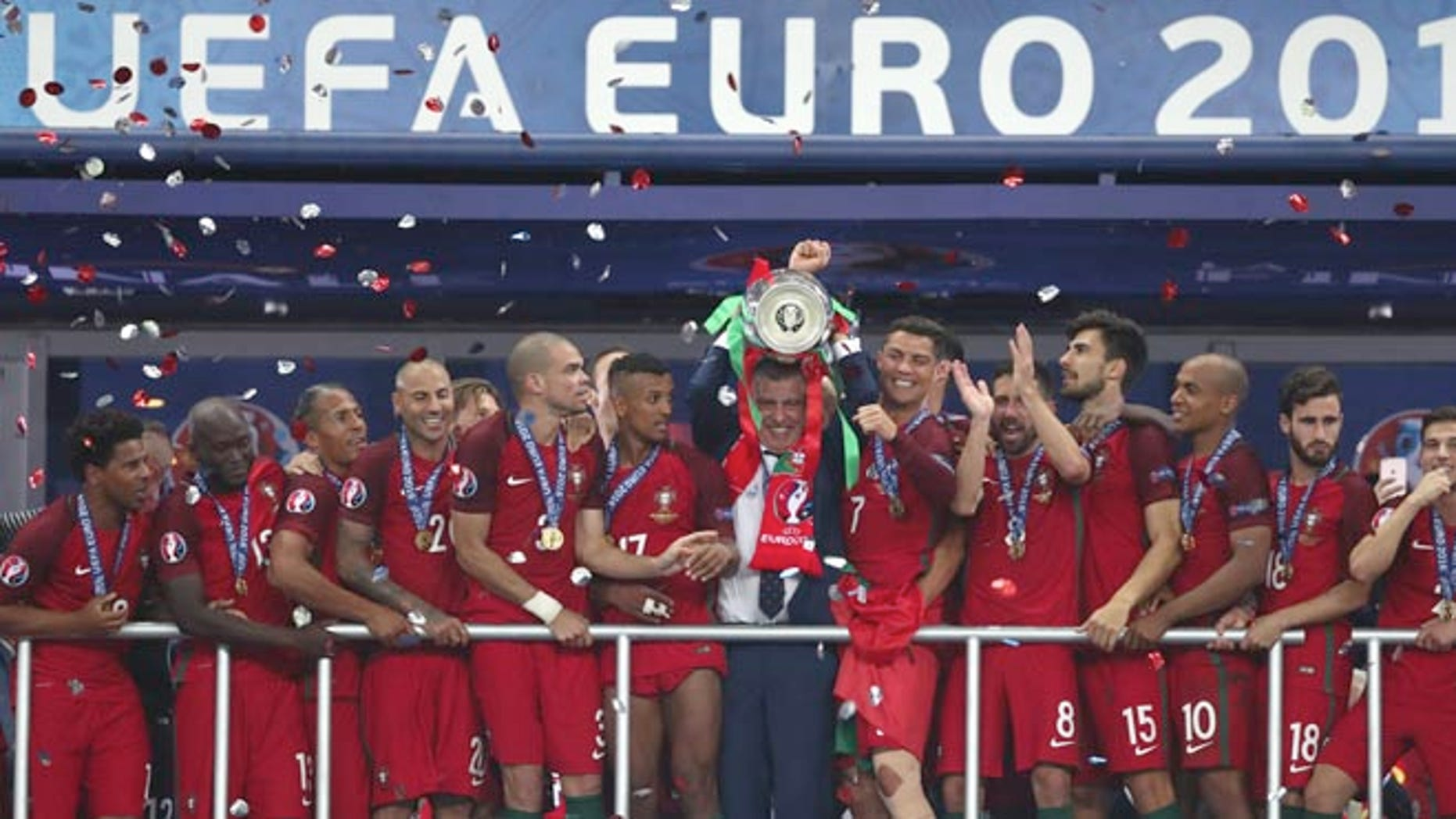 Portugal coach Fernando Santos lifts the trophy between Cristiano Ronaldo, Sunday, July 10, 2016.