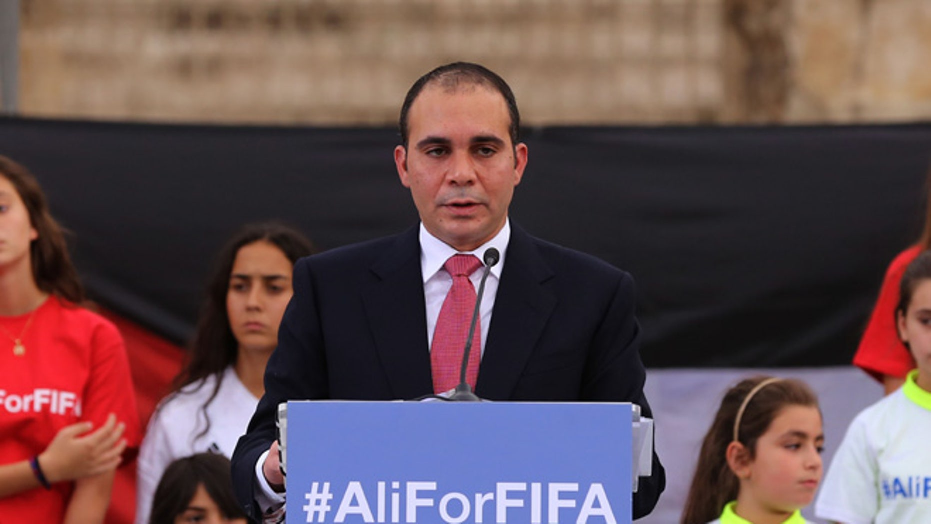 """FILE- In this file photo dated Wednesday, Sept. 9, 2015, Jordan's Prince Ali bin al-Hussein, flanked by school-age soccer players, speaks to about 300 guests during an event at a Roman amphitheater in Amman, Jordan. Seven men are in the running to replace Sepp Blatter as FIFA president, with Michel Platini's candidature accepted but pending because of his suspension from soccer. FIFA published the list of valid applications """"proposed in due time and form"""" on Wednesday Oct. 28, 2015. It did not include former Trinidad and Tobago player David Nakhid, who did not have the five required nominations. he seven candidates for the Feb. 26 election are: Platini, Prince Ali bin al-Hussein, Gianni Infantino, Tokyo Sexwale, Musa Bility, Jerome Champagne and Sheikh Salman bin Ebrahim Al Khalifa.  (AP Photo/Raad Adayleh, FILE)"""