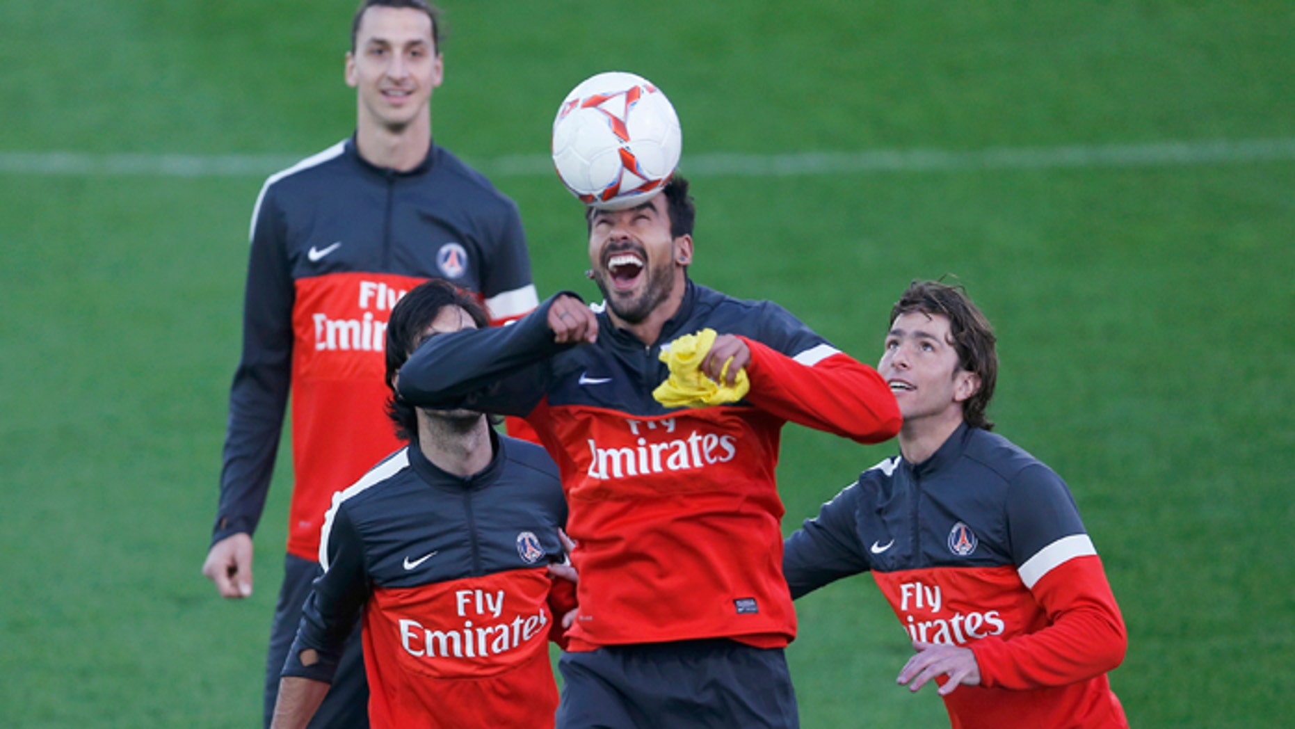 Paris Saint-Germain's Ezequiel Lavezzi heads the ball next as teammates Javier Pastore (L), Zlatan Ibrahimovic (2nd L) and Maxwell (R) watch during a training session.