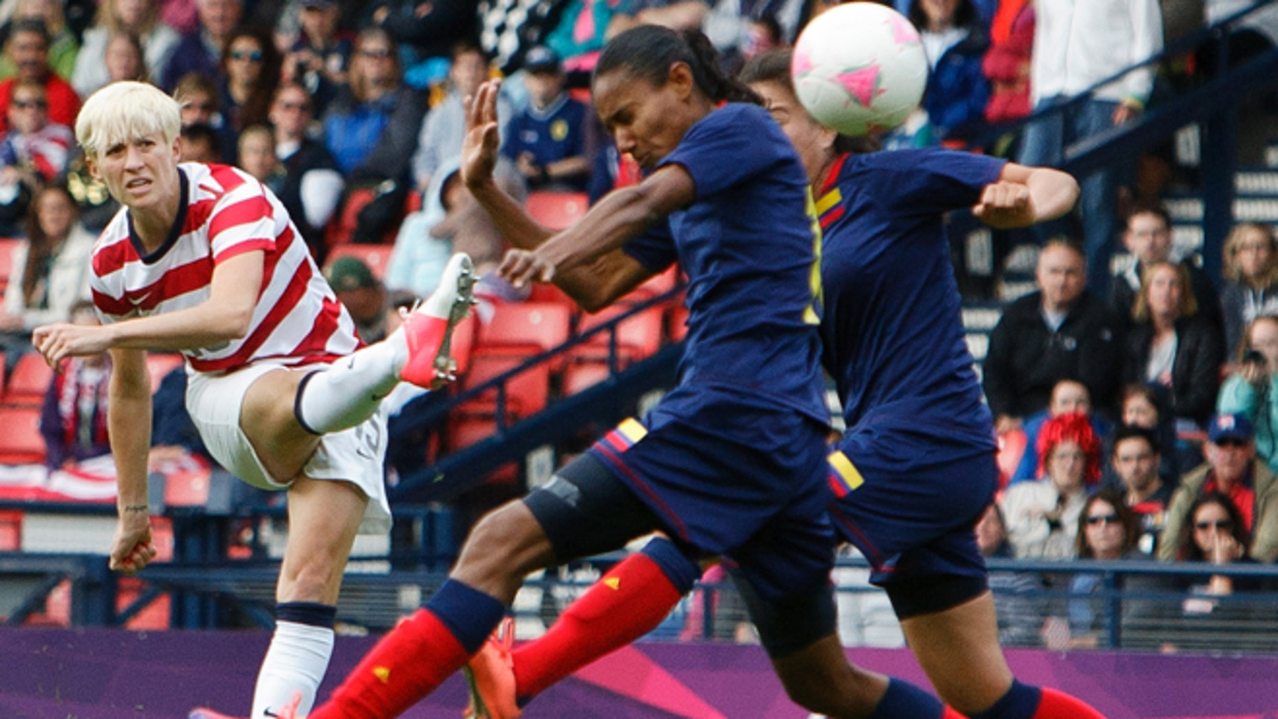 July 28, 2012: United States' Megan Rapinoe, left, shoots and scores the opening goal during the group G women's soccer match between the United States and Colombia at the London 2012 Summer Olympics in Glasgow, Scotland.