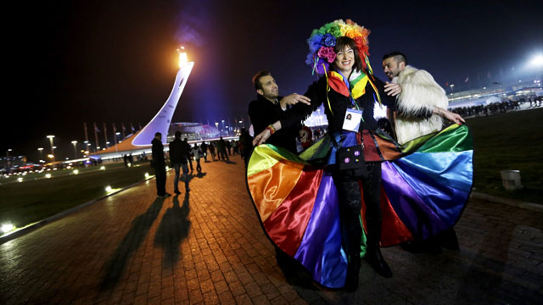 February 17, 2014: Vladimir Luxuria, center, a former Communist lawmaker in the Italian parliament and prominent crusader for transgender rights, is led away by friends to attend a women's ice hockey match after posing for photos on the Olympic Plaza at the 2014 Winter Olympics in Sochi, Russia. Luxuria was soon after detained by police upon entering the Shayba Arena. (AP Photo/David Goldman)