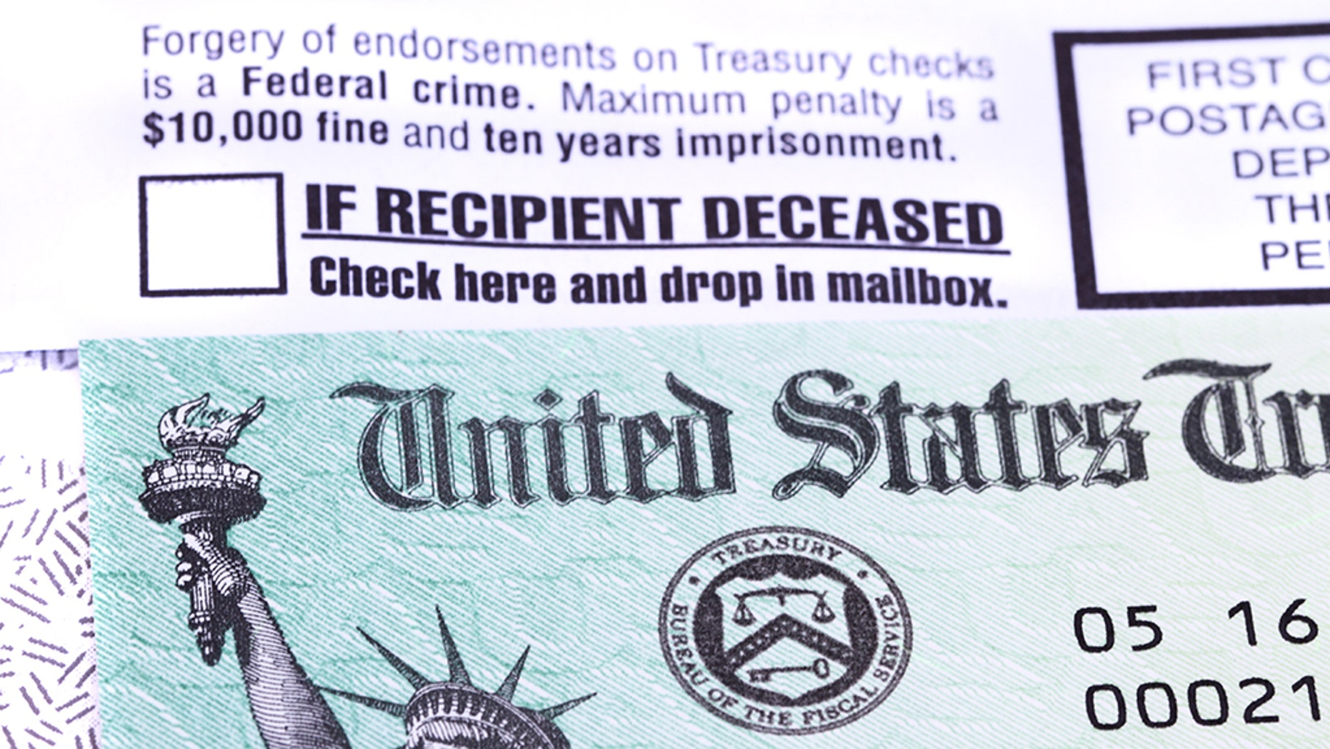 West Palm Beach, USA - June 10, 2014: A United States government Treasury Check used to pay Social Security or Medicare benefits lies on top of the opened envelope used to mail it to the recipient. The envelope has warnings of criminal penalties for anyone who fraudulently endorses the check. It also warns that if the recipient is deceased, the check should be placed in the return mail. The distinctive green checks feature an engraving of the Statue of Liberty and the Treasury Seal.