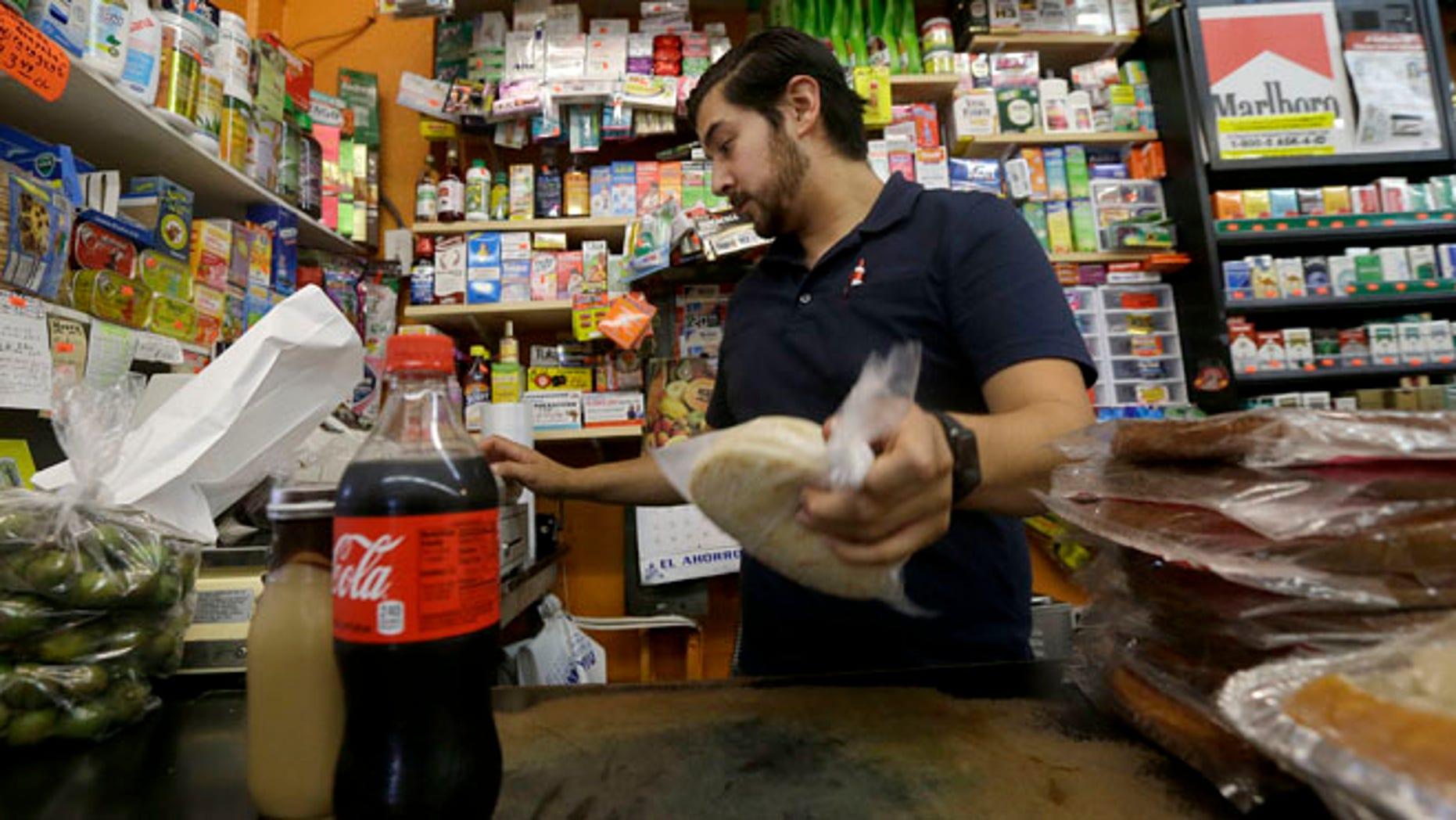 Alex Del Rio works at his family's market El Ahorro in San Francisco, Wednesday, Sept. 21, 2016.