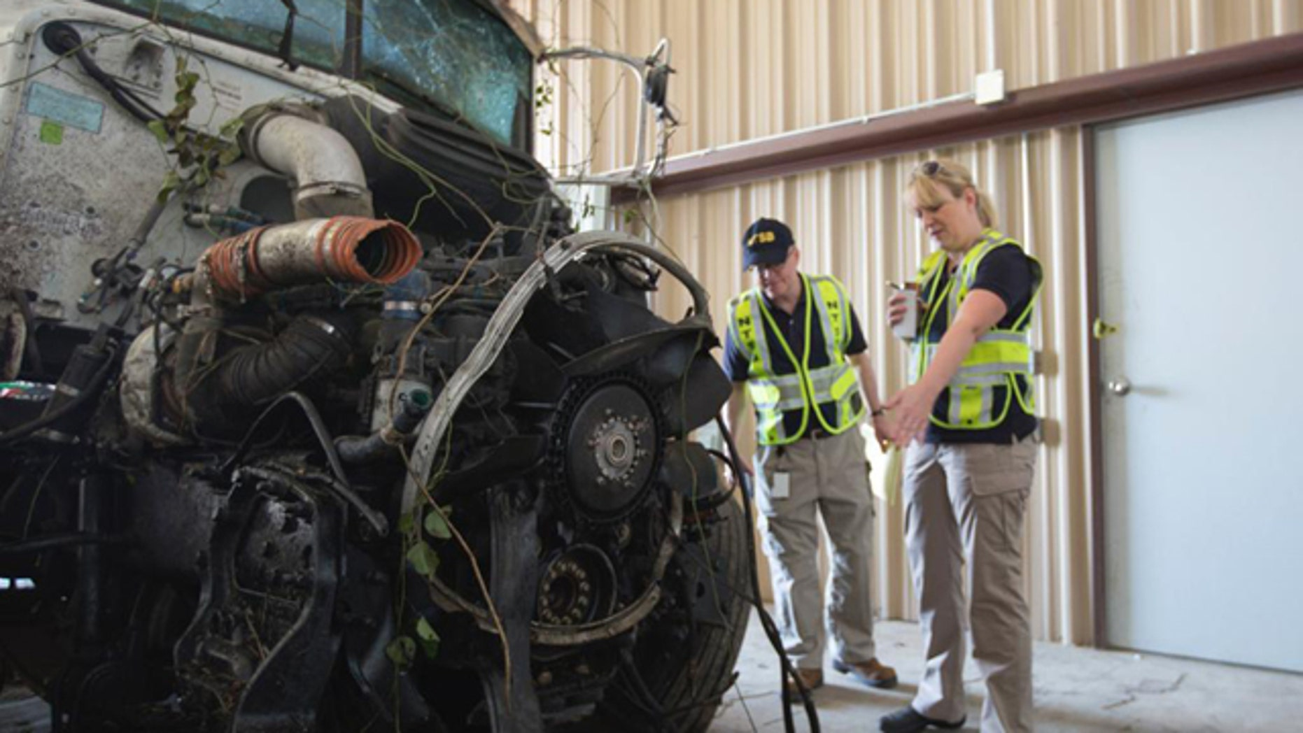 September 27, 2014: In this photo provided by The National Transportation Safety Board, officials examine part of the wreckage involved in a fatal highway accident in Davis, Okla. (AP Photo/National Transportation Safety Board)
