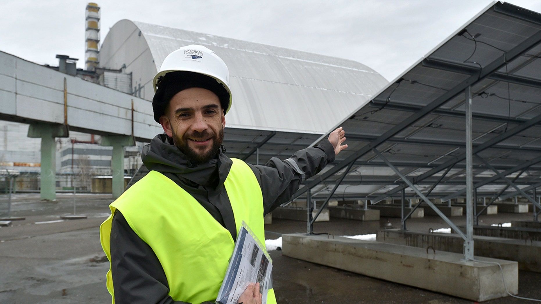 Yevgen Varyagin, the head of the Ukrainian-German company Solar Chernobyl speaks to AFP journalists in front of photovoltaic panels on the new one-megawatt power plant next to the New Safe Confinement over the fourth block of the Chernobyl nuclear plant on December 12, 2017 (GENYA SAVILOV/AFP/Getty Images)