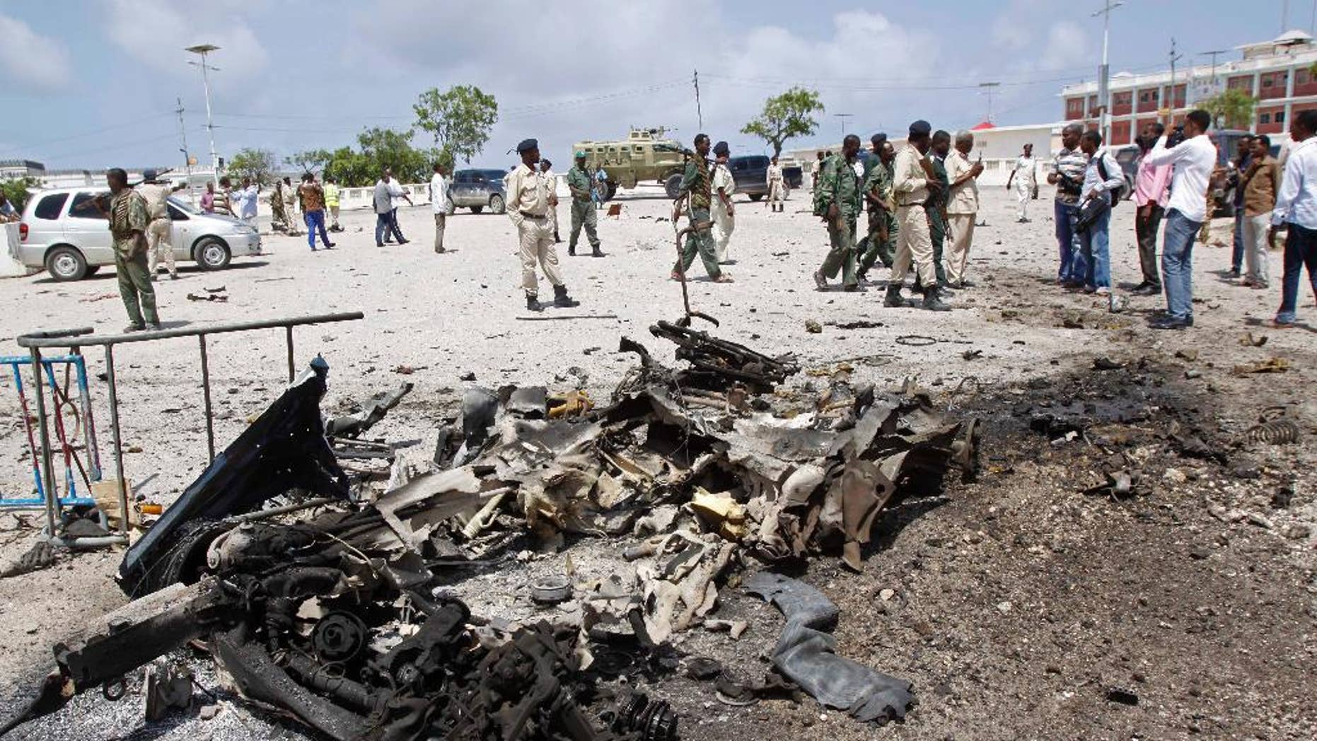 Somali soldiers stand near the wreckage of a suicide car bomb near the Somali parliament in Mogadishu, Somalia, Saturday, July 5, 2014. A Somali police officer says troops have thwarted an attack by a suicide bomber outside the heavily guarded parliament headquarters. Capt. Mohamed Hussein, a senior Somali police officer says troops stopped a suicide car bomber who detonated his explosive-laden car at a checkpoint near the entrance to Somalia's parliament. (AP Photo/Farah Abdi Warsameh)