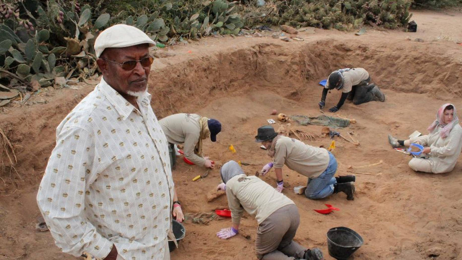 In this photo taken Tuesday, Feb. 18, 2014, Chairman of the Somaliland War Crimes Commission Kadar Ahmed, left, oversees members of the Peruvian Forensic Anthropology Team as they work to uncover bodies buried in a mass grave in Hargeisa, Somaliland, a breakaway region of Somalia.  An American volunteer gently brushes away dirt to reveal the bones of a Somali victim buried in a mass grave some 30 years ago. Tens of thousands of skeletons may lie in mass graves here, on the northern edge of Somalia, where many want to see justice prevail, even if delayed.  Last year 38 bodies were uncovered in two graves by the Somaliland War Crimes Investigation Commission, which is overseeing the work on a third site where another dozen bodies are buried.  (AP Photo/Jason Straziuso)
