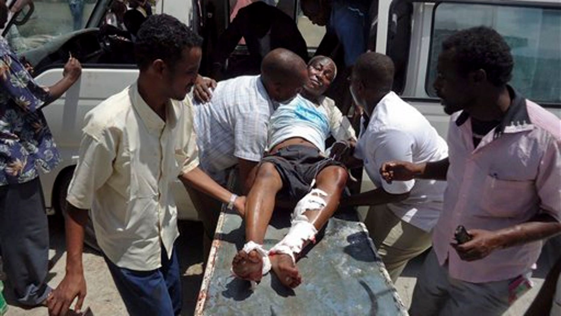April 4, 2012: Medical personnel help a man wounded in a blast at the Somali National Theater in Mogadishu, Somalia.