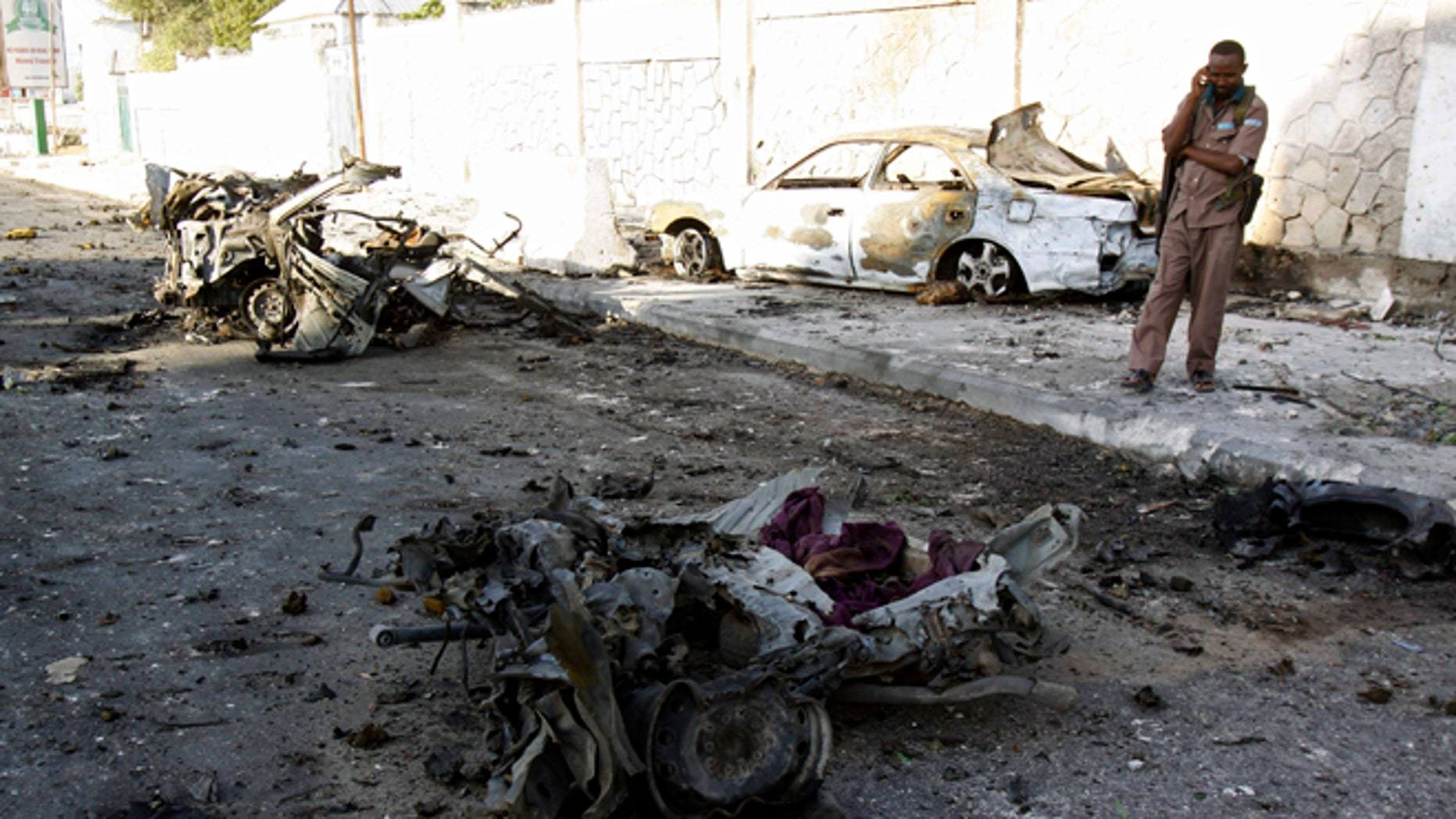 Jan 2, 2013: A Somali soldier stands near the wreckage of cars, after bombs went off at the gate of a hotel in Mogadishu, Somalia.