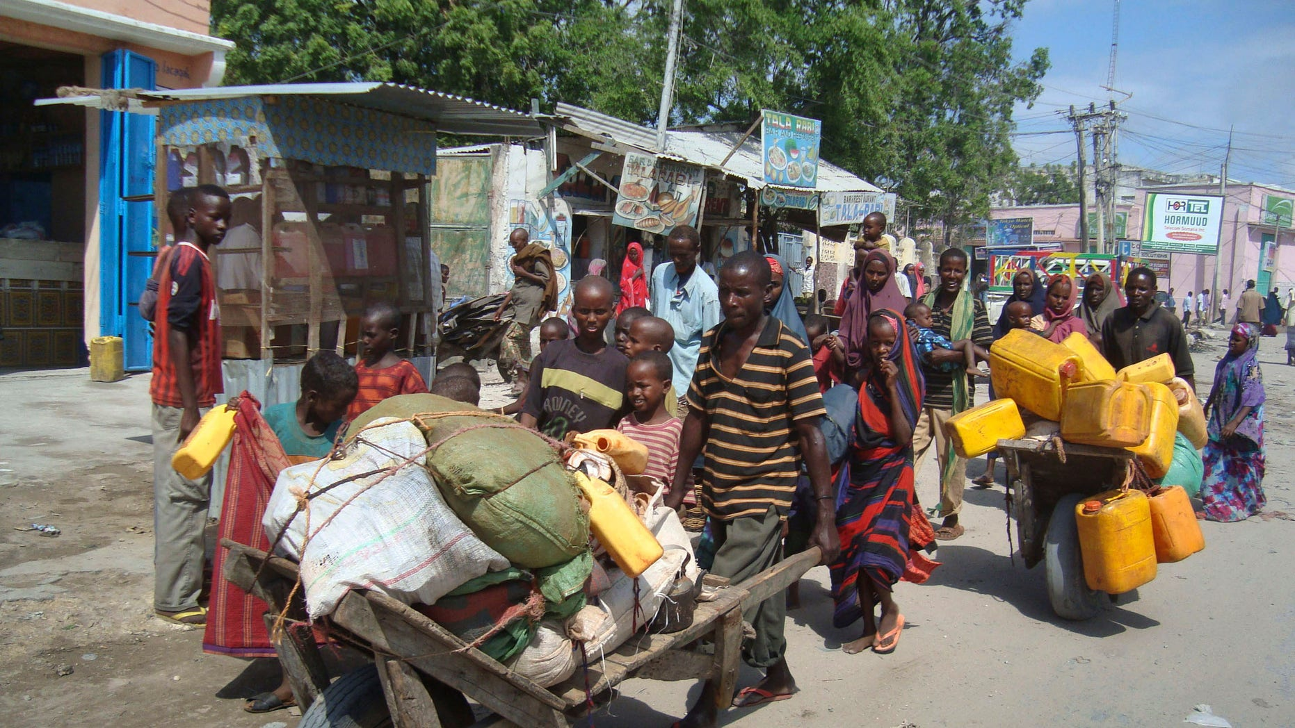 Somalis from southern Somalia carrying their belongings make their way to a new camp for internally displaced people in Mogadishu Somalia, Thursday July, 28, 2011.