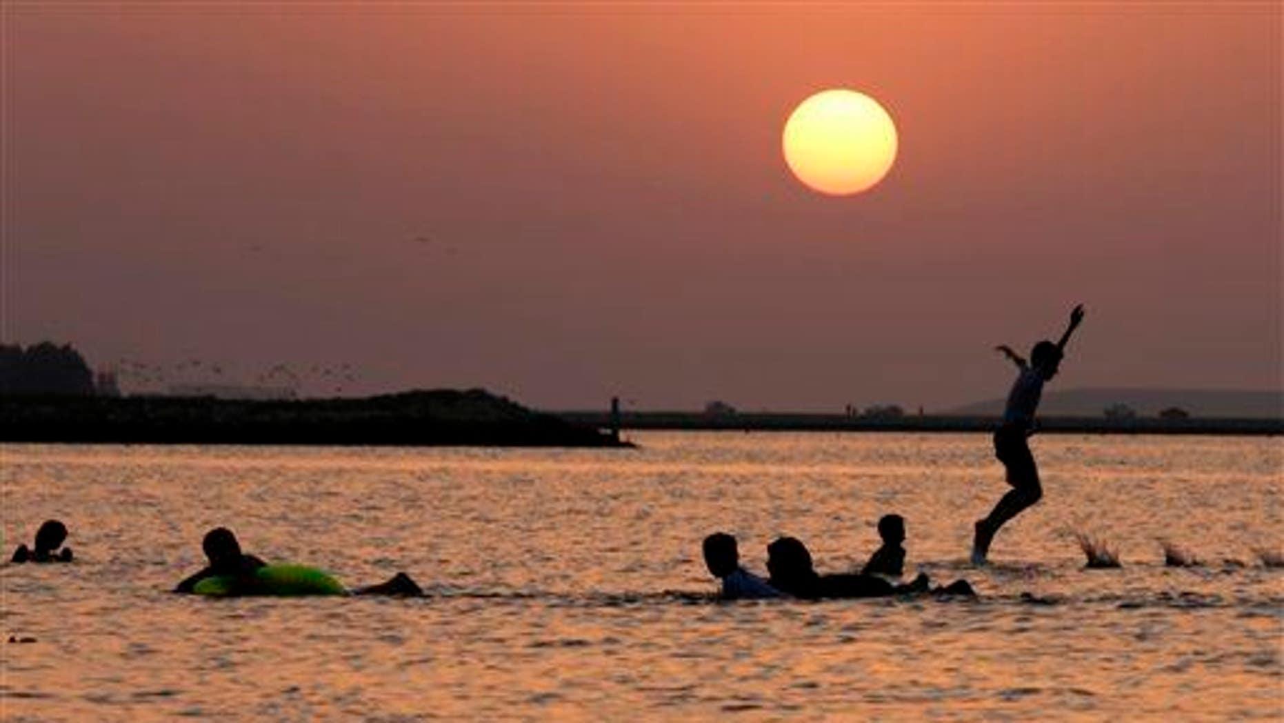 Bahraini children play along the Persian Gulf shore as the sun sets in Karranah, Bahrain, on Sept. 20, 2014.