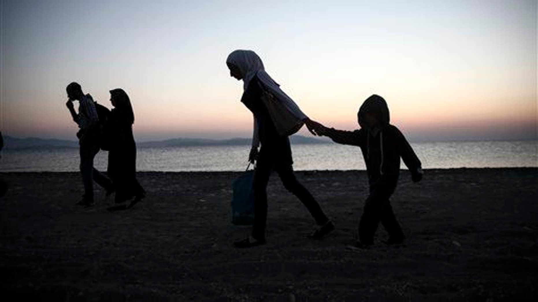 People walk along a beach on the Greek southeastern island of Kos, Wednesday, Aug. 12, 2015.