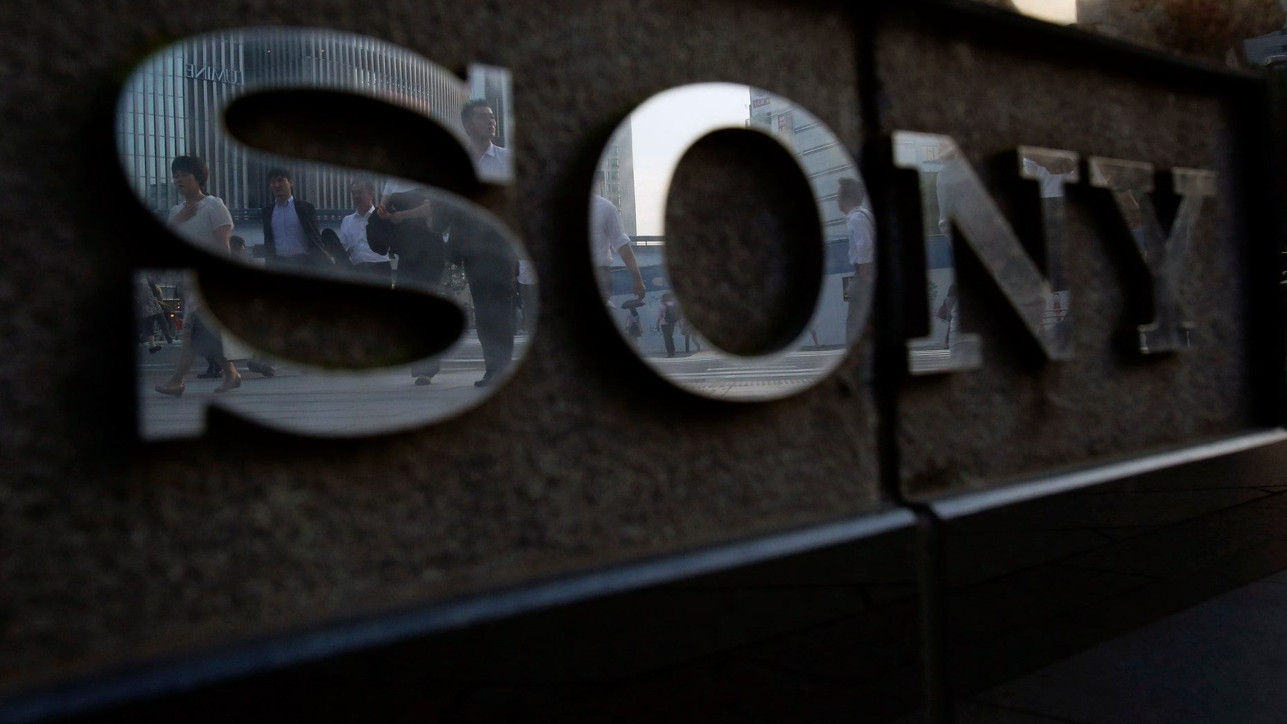 Pedestrians are reflected in a logo of Sony Corp outside its showroom in Tokyo July 16, 2014. Japan's Sony Corp is hammering out plans to rise from the ashes of nearly $10 billion lost in six years by building a future around its last consumer electronics blockbuster - the PlayStation. Sony plans to reposition the video console warhorse as a hub for a network of streamed services, according to three senior officials, offering social media, movies and music as well as games. The executives spoke to Reuters on condition they not be named because the matters are still in early stages of discussion.  Picture taken July 16, 2014. REUTERS/Yuya Shino (JAPAN - Tags: BUSINESS LOGO) - RTR40G1E