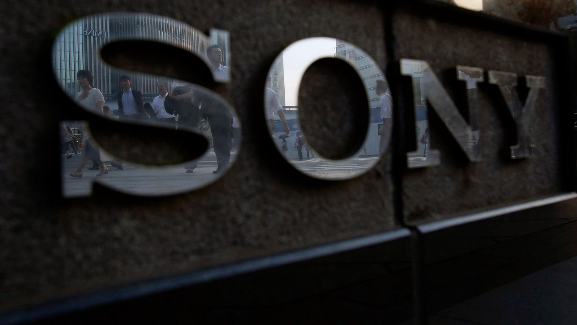 File photo - Pedestrians are reflected in a logo of Sony Corp outside its showroom in Tokyo July 16, 2014.