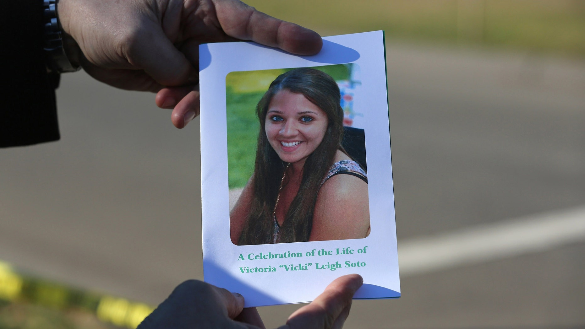 Dec. 19, 2012: A mourner displays a program for the funeral of slain teacher Victoria Soto, 27.