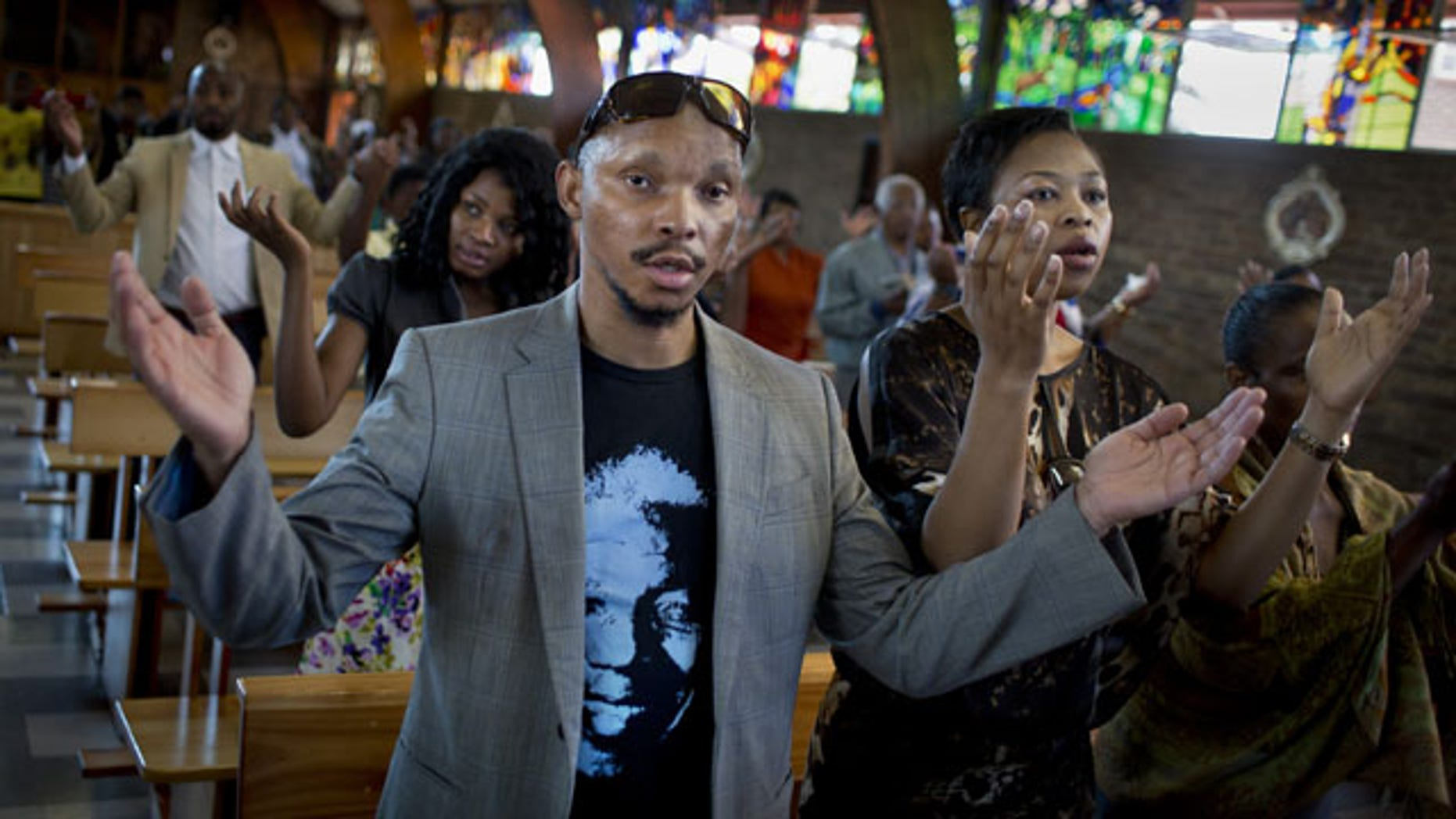 "December 8, 2013: Mourners attend an early morning church service in memory of Nelson Mandela at the Regina Mundi church, which became one of the focal points of the anti-apartheid struggle, in Soweto, Johannesburg, People in South Africa are taking part in a day of ""prayer and reflection"" for late President Nelson Mandela. (AP Photo/Ben Curtis)"