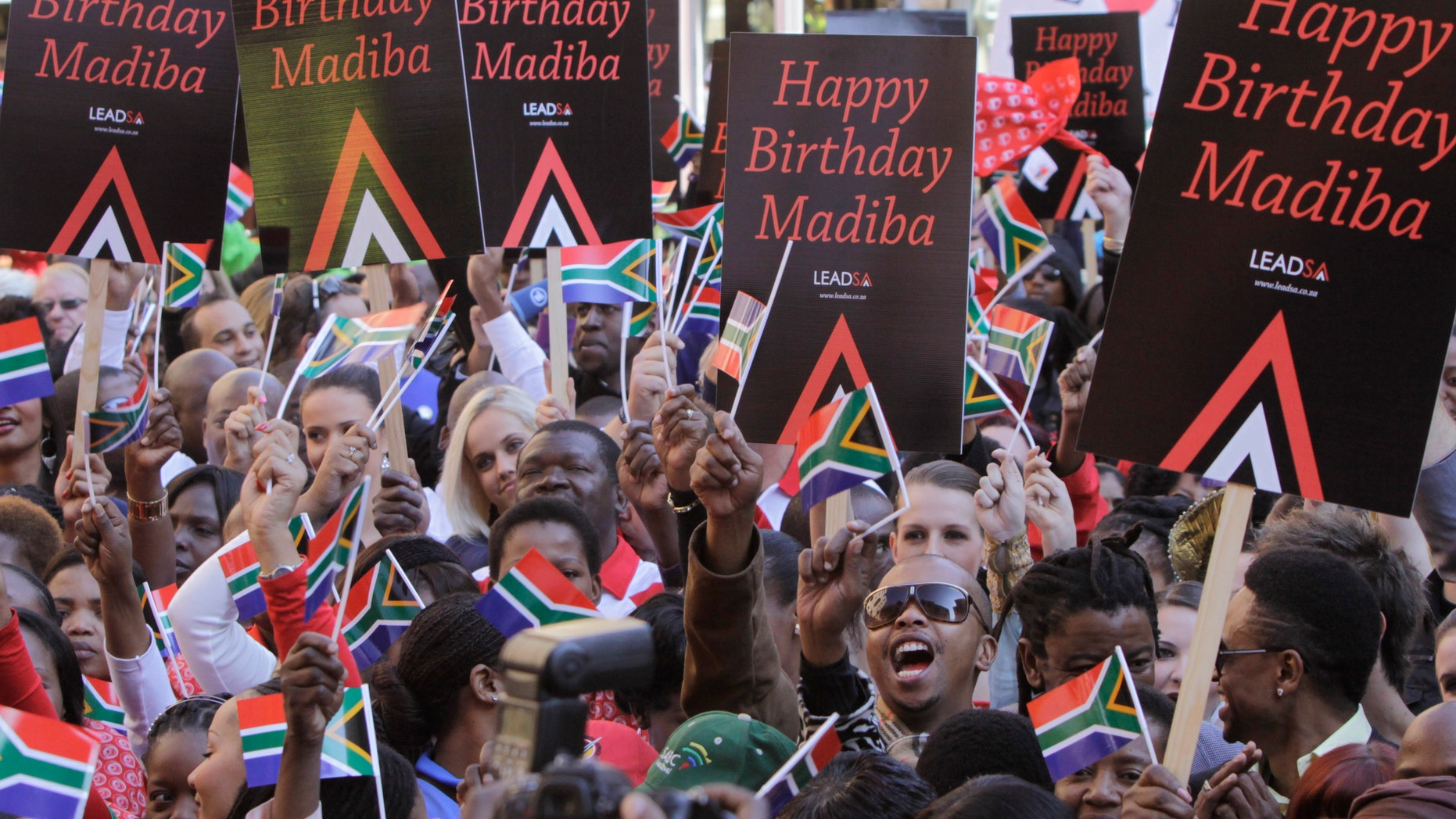 """In this photo taken Friday June 1, 2012,  members of the public and celebrities gather to videotape a sing-a-long birthday wish for former president Nelson Mandela, portrait on woman's shirt, on Nelson Mandela Square in Johannesburg. Mandela's office on Monday June 18 2012 has released the video of South Africans singing """"Happy Birthday"""" in an effort to motivate people around the world to salute the anti-apartheid icon ahead of his 94th birthday next month. (AP Photo/Denis Farrell)"""