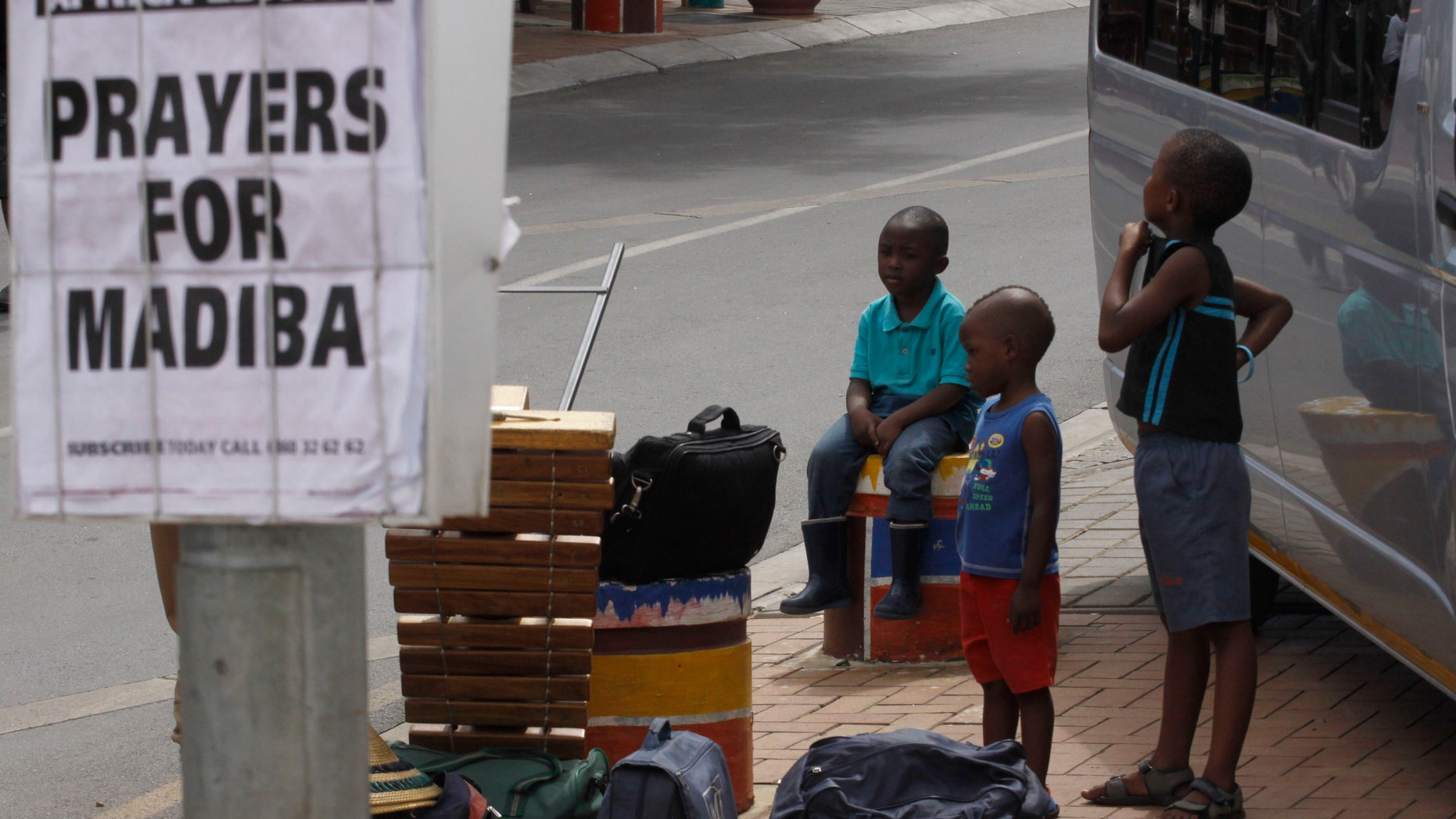 Dec 10, 2012 - Children hang out next to newspaper headline in tourist hub of Soweto South Africa, where Nelson Mandela once lived. Mandela is affectionately known as Madiba.