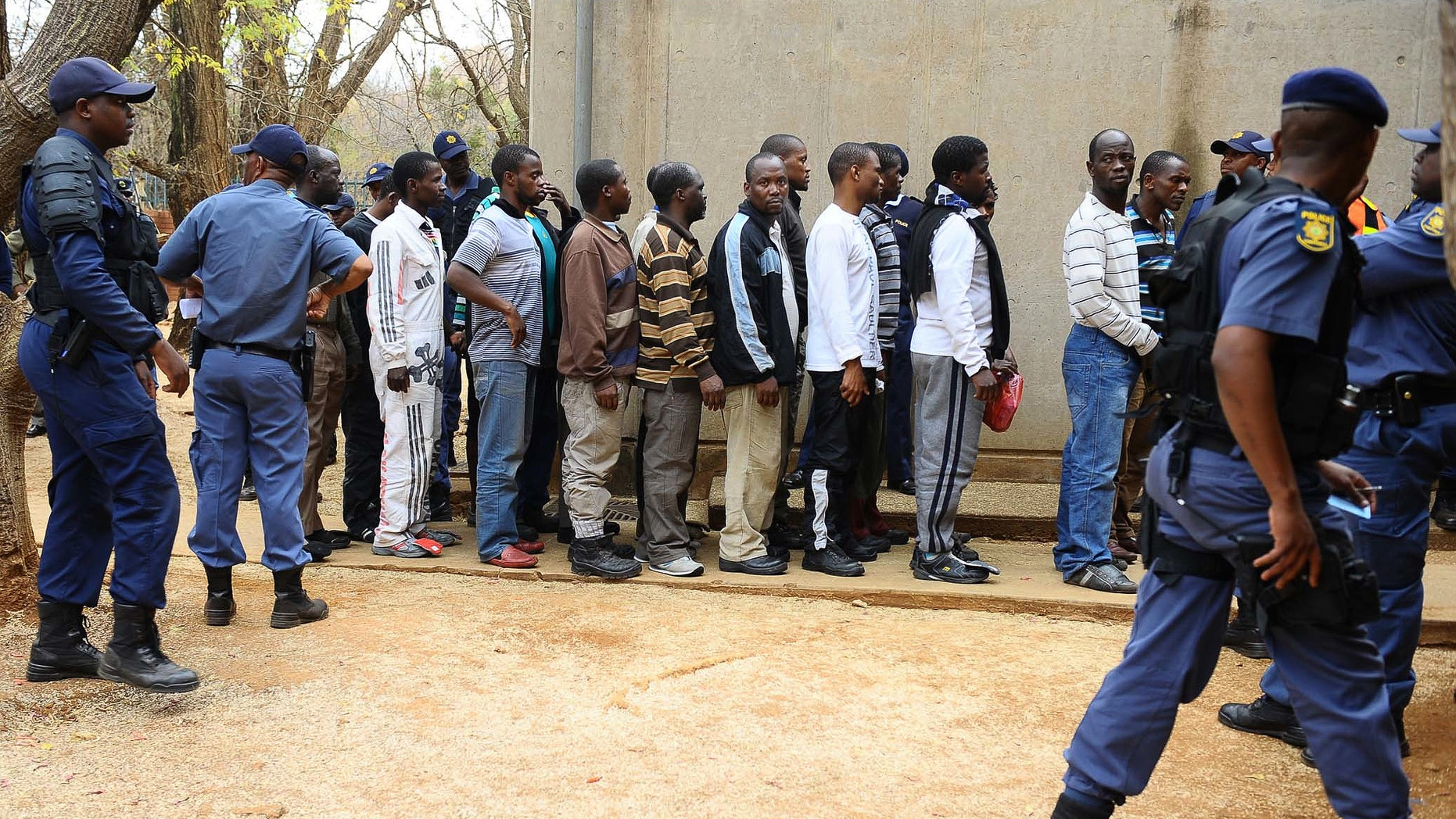 Aug. 27, 2012: Unidentified arrested mine workers await to be escorted into the court by police offers at the Ga-Rankuwa Magistrate Court in Pretoria, South Africa.