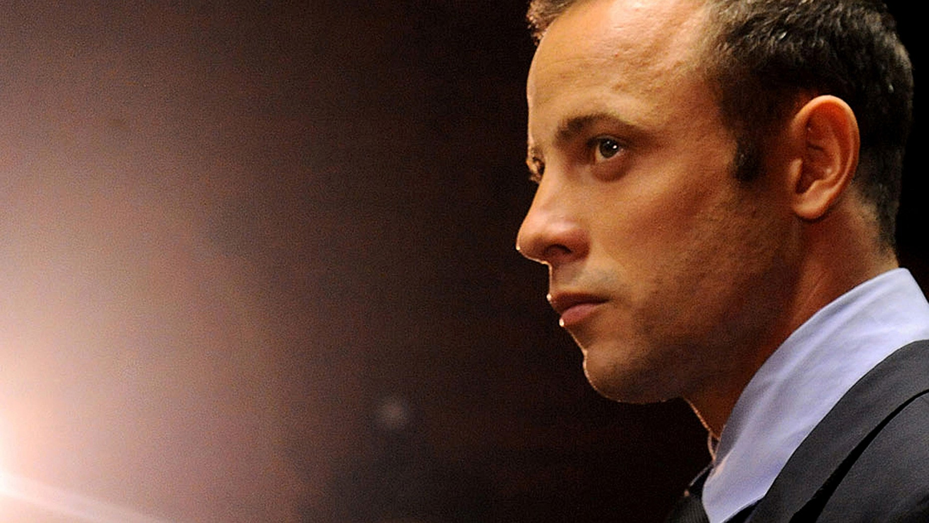 FILE - In this Friday, Feb. 22, 2013 file photo Olympic athlete Oscar Pistorius stands in the dock during his bail hearing at the magistrates court in Pretoria, South Africa. Pistorius is scheduled to re-appear in a South African court on Monday Aug.19, 2013. The the 26-year-old double-amputee Olympian will be indicted on a main charge of premeditated murder of his his girlfriend, Reeva Steenkamp. According to reports Sunday Aug.18, prosecutors have confirmed they will maintain the charge they initially laid against Pistorius (AP Photo/Themba Hadebe, File)