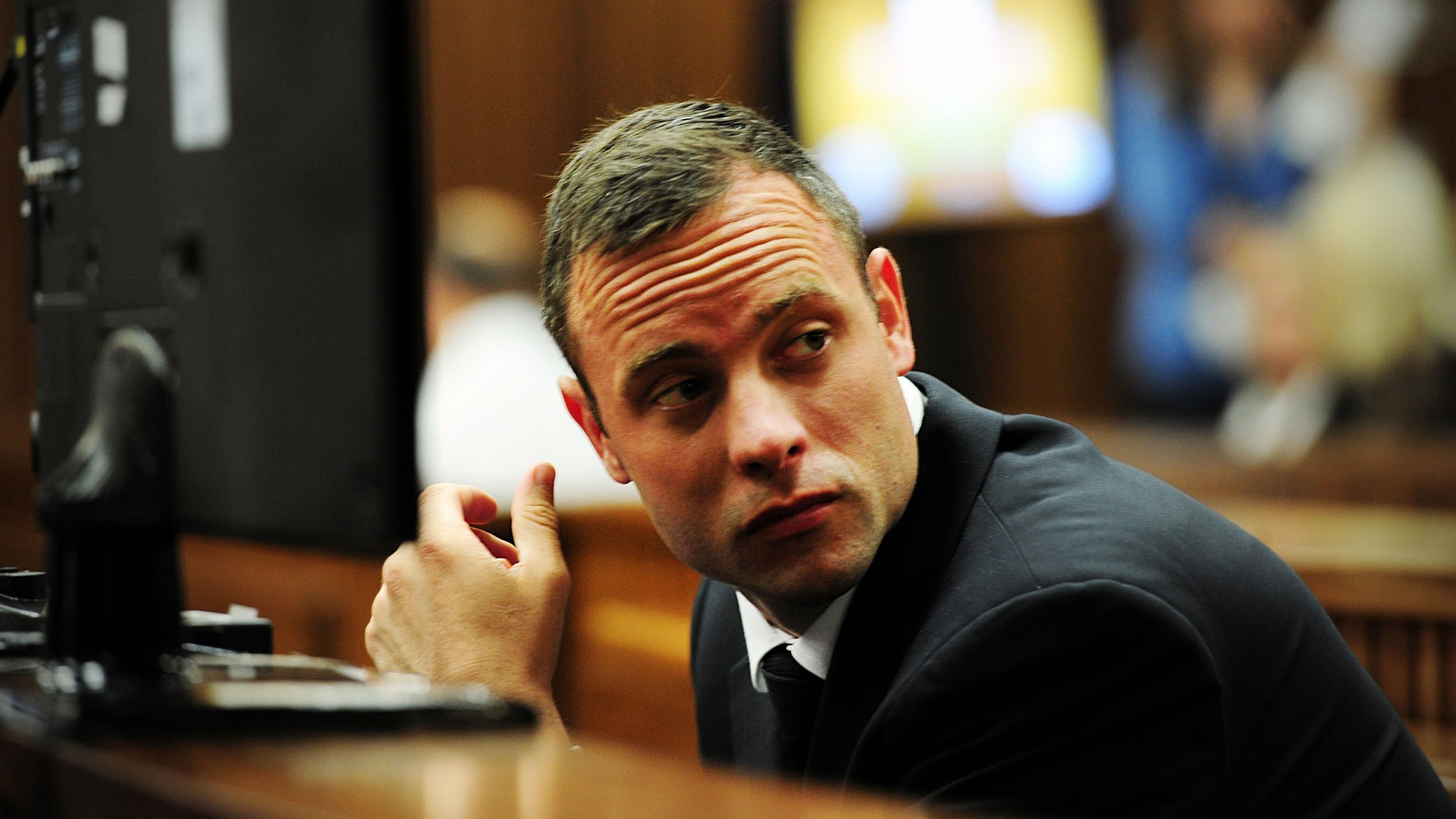 Oscar Pistorius glances sideways as he listens to ballistic evidence being given in court in Pretoria, South Africa, Wednesday, March 19, 2014. Pistorius is on trial for the murder of his girlfriend Reeva Steenkamp on Valentine's Day in 2013. (AP Photo/Leon Sadiki, Pool)