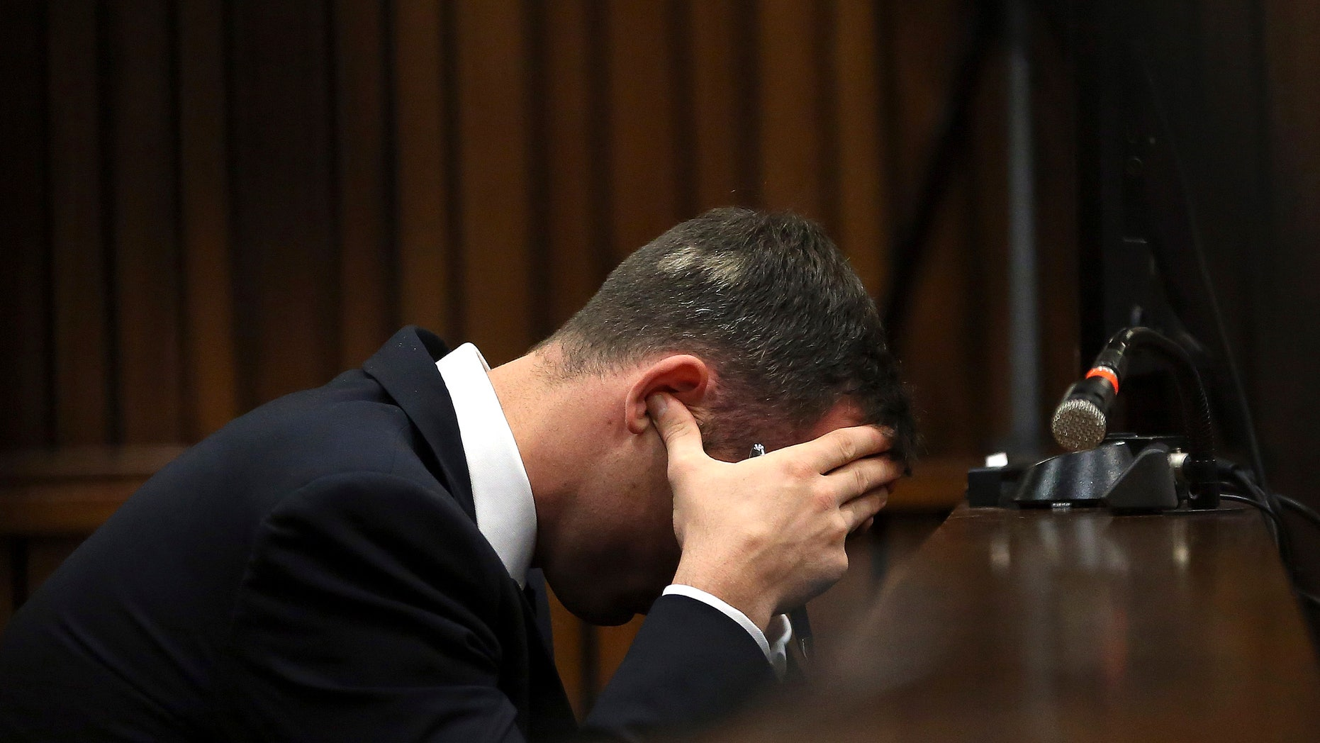 March 19, 2014: Oscar Pistorius, cradles his head in his hands as he listens to ballistic evidence being given in the court during his murder trial in Pretoria, South Africa.