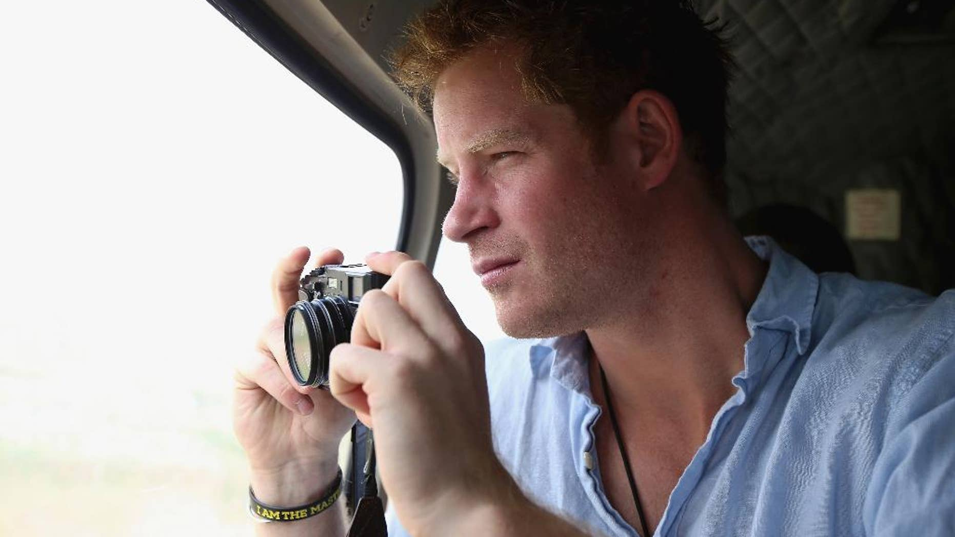 FILE - In this Dec 8, 2014, file photo, Prince Harry takes a photograph out of the window of a helicopter as he travels over the Muluti Mountains on his way to visit a herd boy night school constructed by his Sentebale charity, in Mokhotlong, Lesotho. Prince Harry has been on a private visit to Kruger National Park, South Africa's flagship wildlife park, where poachers have killed rhinos in record numbers and clashed with rangers, the service said in a statement emailed Thursday, Aug. 13, 2015, to The Associated Press. (Chris Jackson/Pool Photo via AP, File)