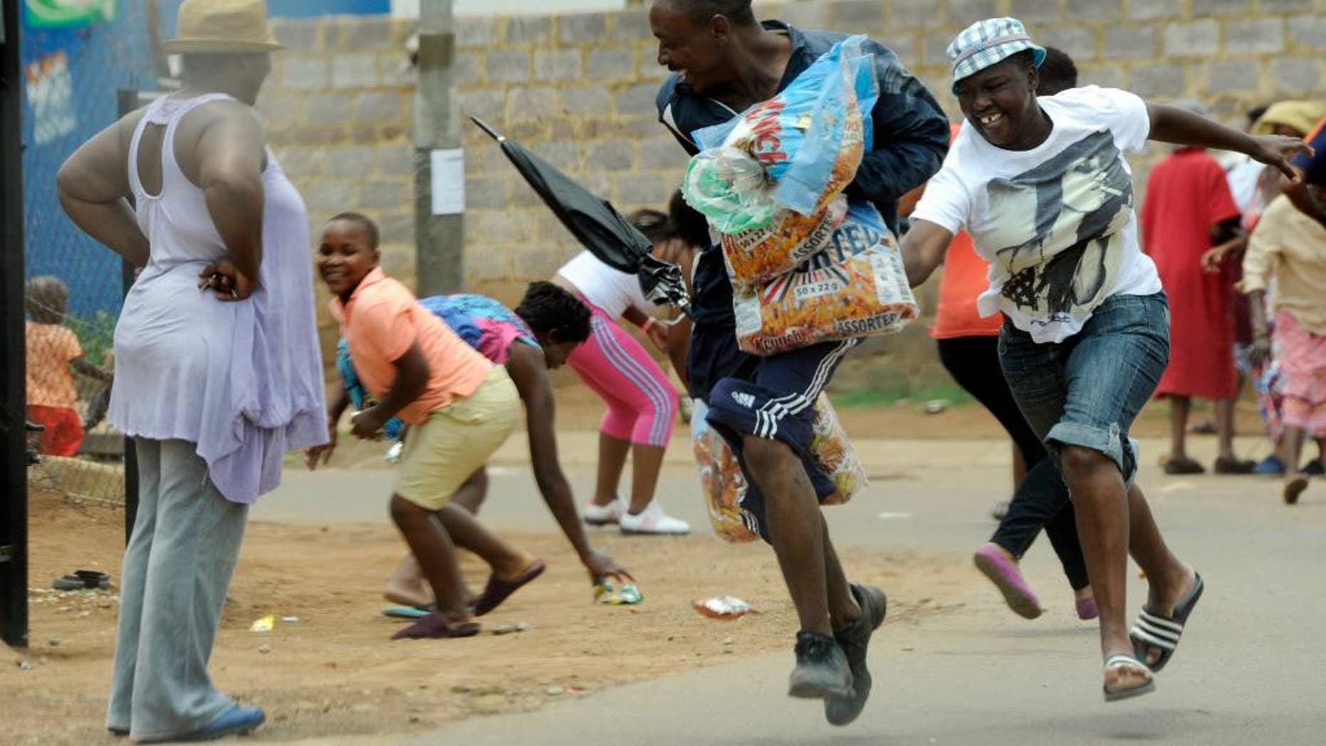 Looters make off with goods from a store in Soweto, South Africa, Thursday, Jan 22, 2015. About 70 people in South Africa have been arrested because of violent protests and looting, much of which was aimed at shops owned by nationals from other African countries, local media reported Thursday. (AP Photo) SOUTH AFRICA OUT NO SALES  NO ARCHIVES