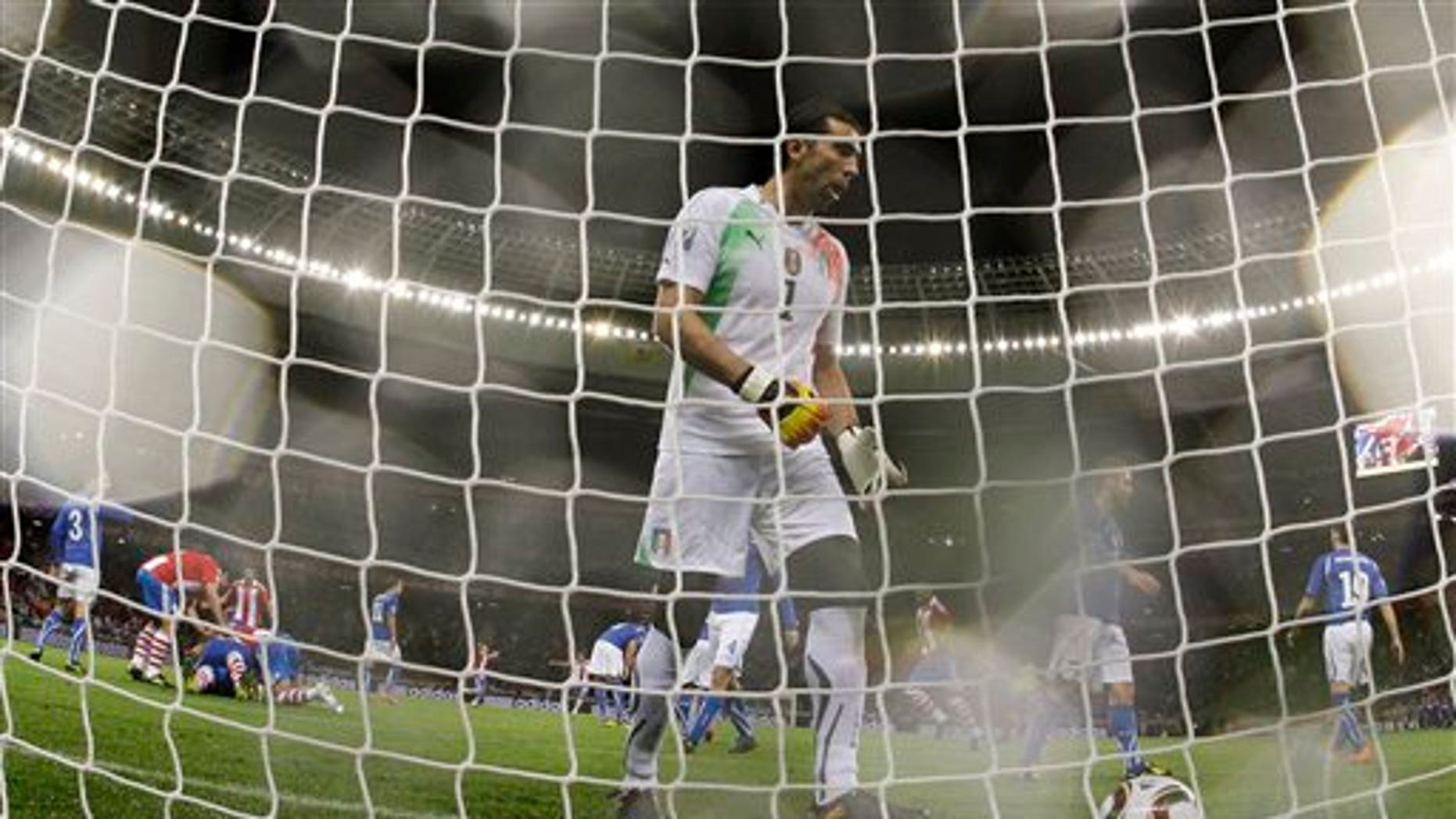 Italy goalkeeper Gianluigi Buffon, center, goes to pick up the ball after a penalty goal by Paraguay's Antolin Alcaraz, as fellow team members pile on top of him to celebrate, at left, during the World Cup group F soccer match between Italy and Paraguay in Cape Town, South Africa, Monday, June 14, 2010.  (AP Photo/Roberto Candia)