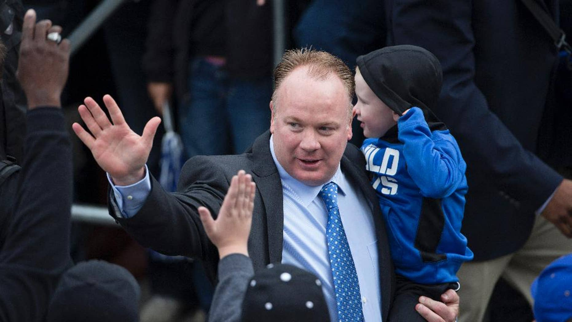 Kentucky head coach Mark Stoops, holding his son Zack, waves to fans as he walks into the stadium for an an NCAA college football game against South Carolina at Commonwealth Stadium in Lexington, Ky., Saturday, Oct. 4, 2014. (AP Photo/David Stephenson)