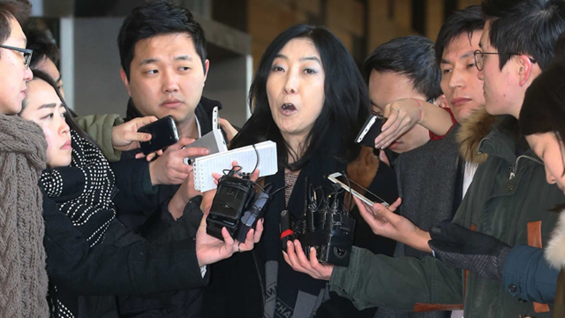 Jan. 7, 2015: California-resident Shin Eun-mi, center, talks to reporters at Seoul District Prosecutors' Office. South Korean officials say they were considering whether to deport the Korean-American woman accused of praising rival North Korea during a recent lecture. (AP Photo/Yonhap, Park Ji-ho)