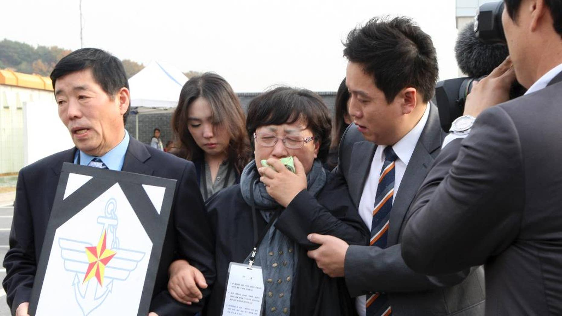 A mother, center, of a victim, identified as Private First Class Yoon, cries after the trial at an outside of military court in Yongin, south of Seoul, South Korea, Thursday, Oct. 30, 2014. South Korea's Defense Ministry says a military court has sentenced six soldiers to up to 45 years in prison for bullying and beating a subordinate who died. (AP Photo/Yonhap, Ryu Soo-hyun) KOREA OUT