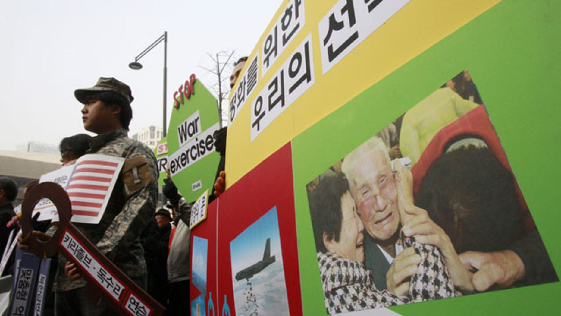 February 24, 2014: With a picture of South and North Korean family's reunion on display, protesters stage a rally denouncing the annual joint military exercises, dubbed Key Resolve and Foal Eagle, between South Korea and the United States, near the U.S. Embassy in Seoul, South Korea. (AP Photo/Ahn Young-joon)