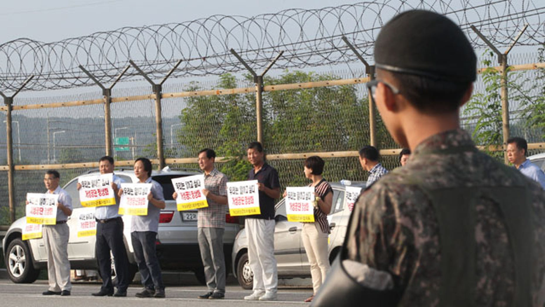 August 14,2013: South Korean owners who run factories in the stalled South Korea and North Korea's joint Kaesong Industrial Complex hold signs as they demand South Korean government and North Korean authorities normalize the operation of the joint industrial complex