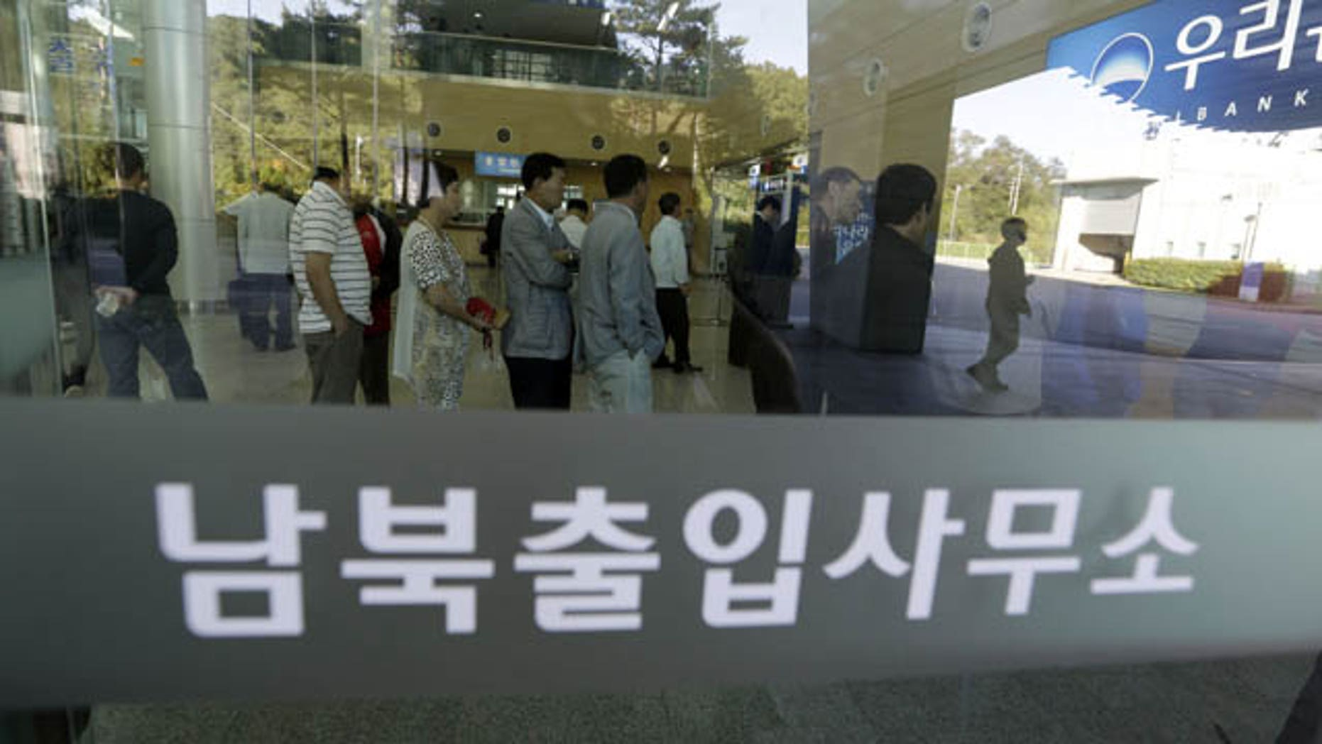 September 16, 2013: South Koreans wait in line to exchange money in front of a bank before leaving for the Kaesong Industrial Complex at the Inter-Korean Transit Office near the border village of Panmunjom, which has separated the two Koreas since the Korean War. (AP Photo)