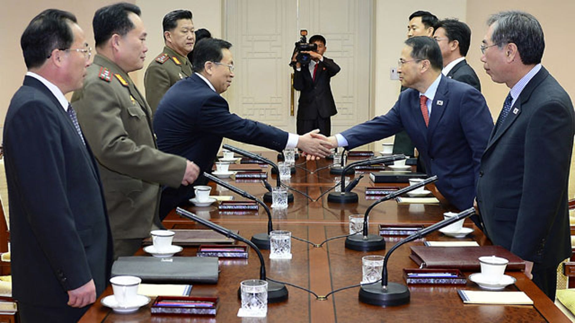 February 12, 2014: In this photo released by the South Korean Unification Ministry, South Korean chief delegate Kim Kyou-hyun, second from right, shakes hands with his North Korean counterpart Won Tong Yon, third from left, during their meeting at the border village of Panumjom, South Korea. (AP Photo/South Korean Unification Ministry)