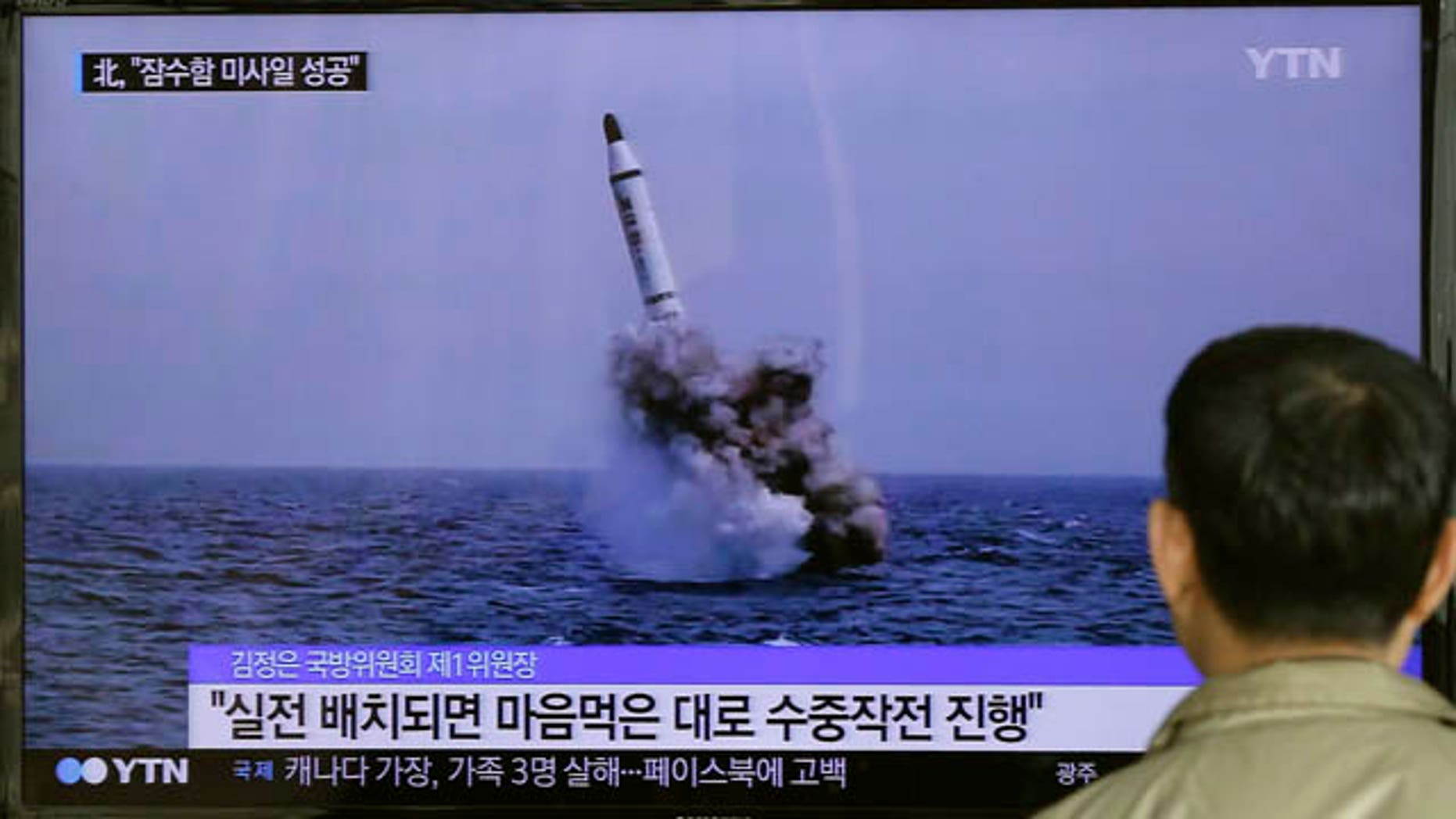May 9, 2015: A South Korean man watches a TV news program showing an image published in North Korea's Rodong Sinmun newspaper of North Korea's ballistic missile believed to have been launched from underwater, at Seoul Railway station.(AP Photo/Ahn Young-oon)
