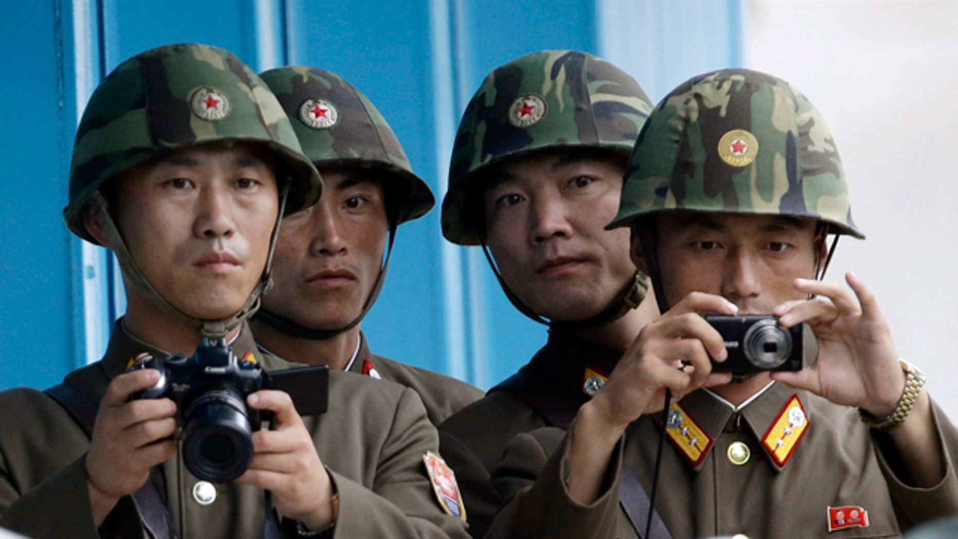 In this Saturday, July 27, 2013 photo, North Korean soldiers watch the southern side with cameras at the border village of Panmunjom, which has separated the two Koreas since the Korean War, in Paju, South Korea. (AP Photo/Lee Jin-man)