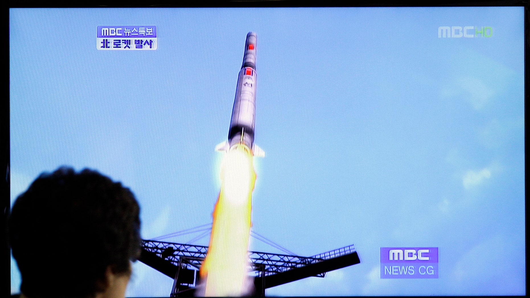 April 13, 2012: A South Korean woman watches a TV news report showing a computer generated image of North Korea's long-range rocket at Seoul train station in Seoul, South Korea.