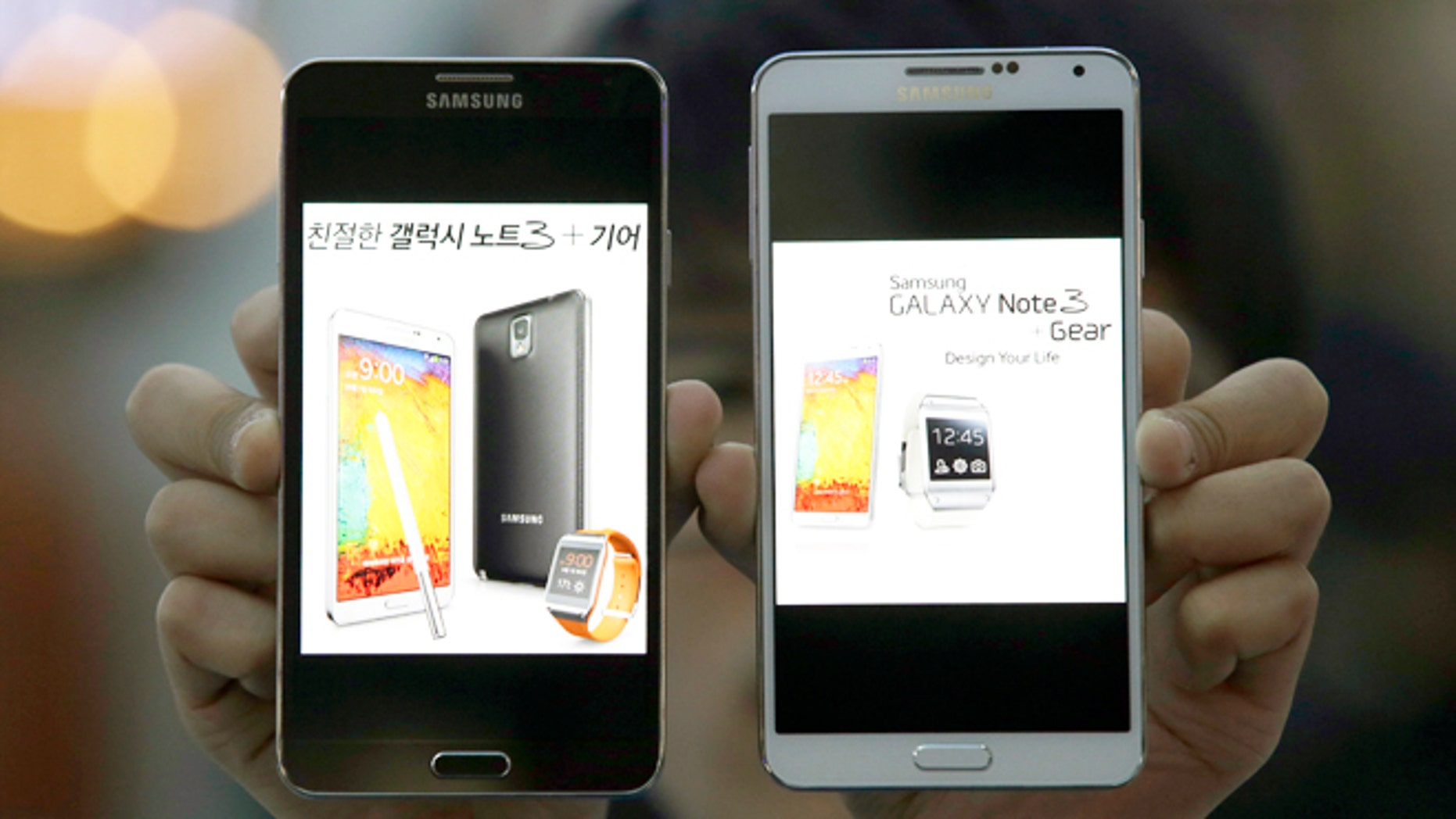 Oct. 23, 2013: An employee of Samsung Electronics holds two Galaxy Note 3 smartphones while posing for photos at a train station in Seoul, South Korea.