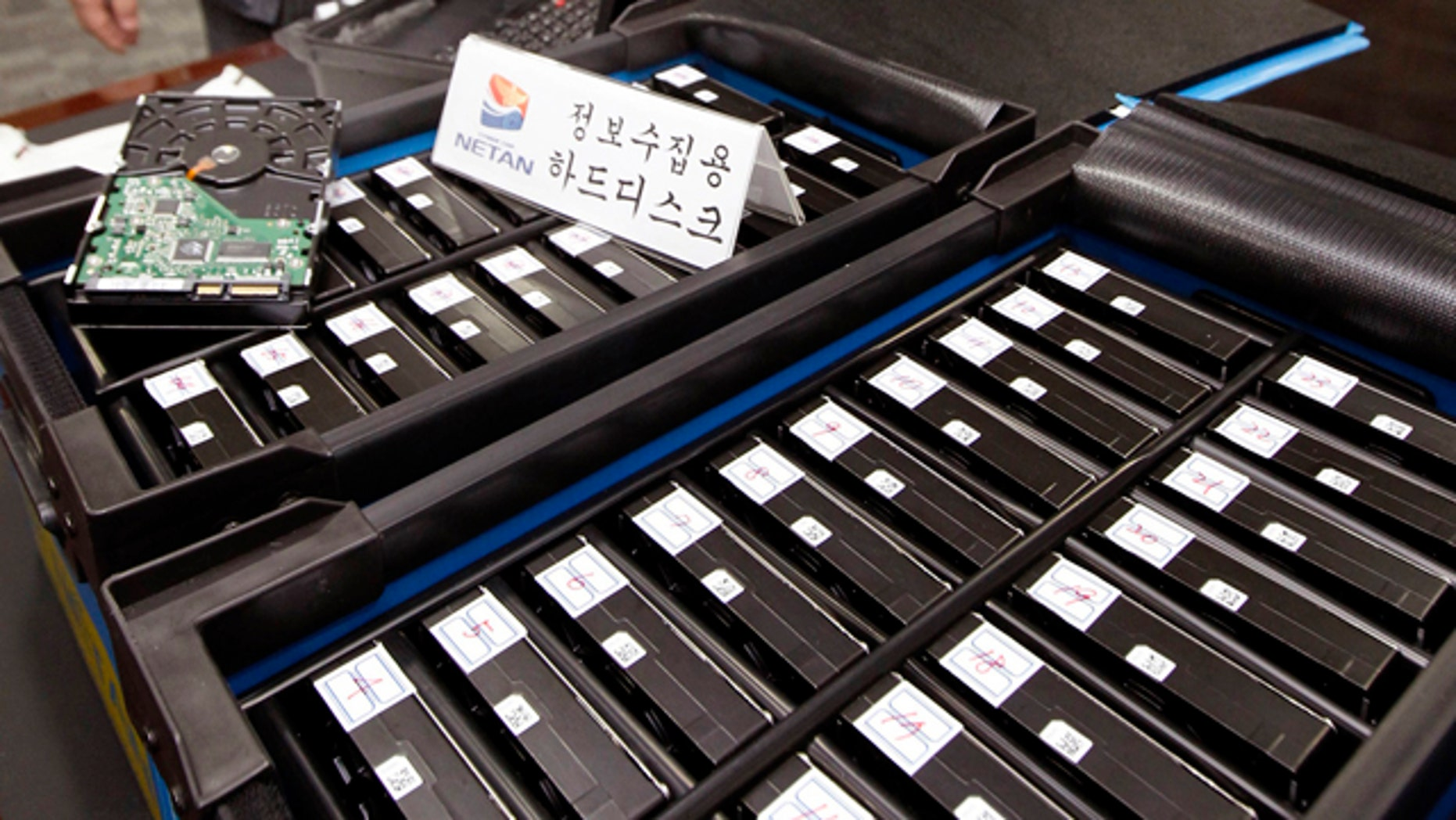 "South Korean officials from the National Police Agency's Cyber Terror Response Center show some of the hard disks taken from the office of Google Korea at the headquarter of the National Police Agency in Seoul, South Korea. Google has been accused of collecting e-mails and other personal information from unsecured wireless networks while it took photos of neighborhoods in South Korea for its ""Street View"" mapping service."