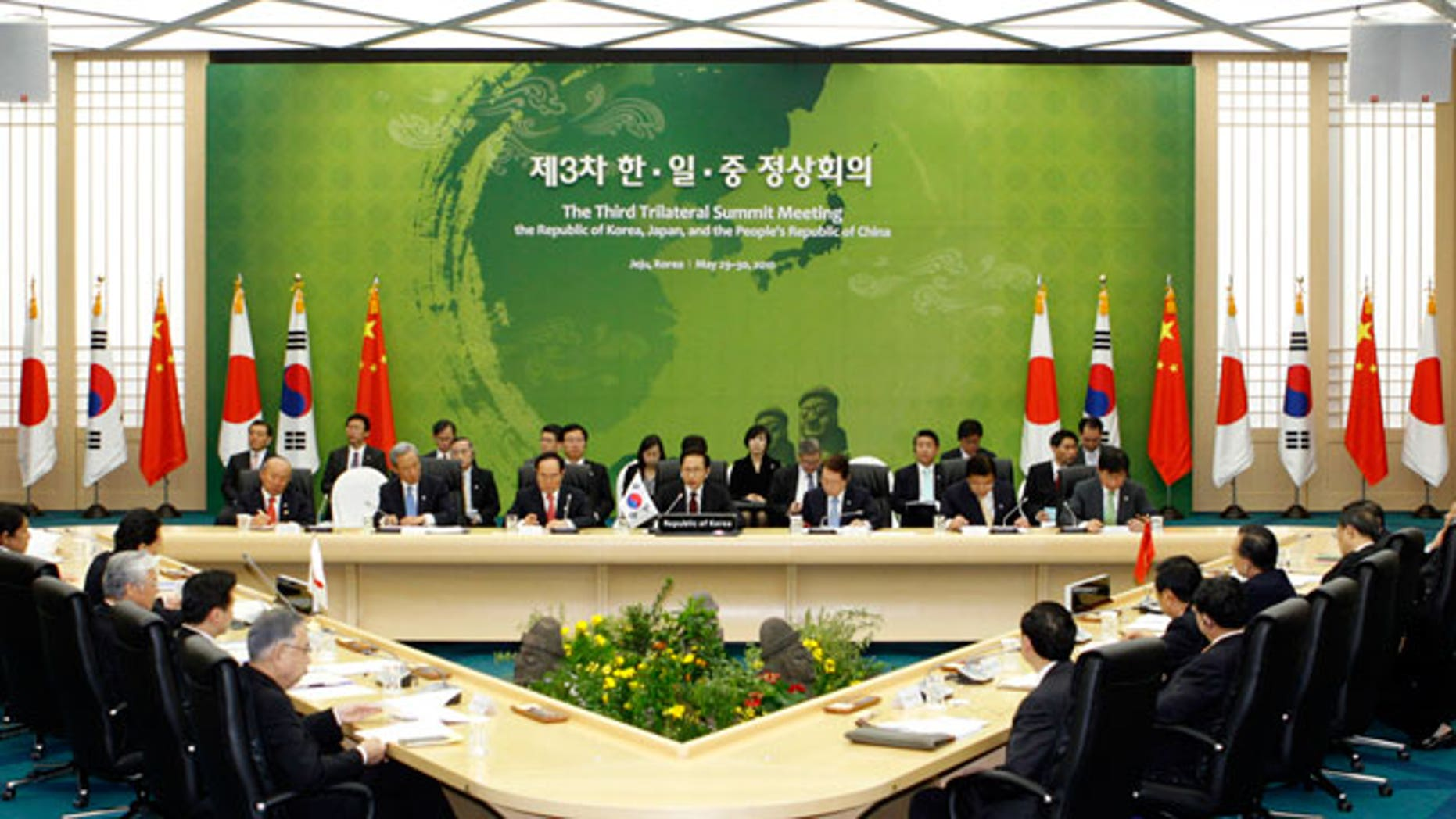 Officials from South Korea, background, Japan, left, and China participate in the trilateral summit in Seogwipo on Jeju island, South Korea, Sunday, May 30, 2010. South Korean President Lee Myung-bak, Japanese Prime Minister Yukio Hatoyama and Chinese Premier Wen Jiabao met Sunday on the last day of a summit expected to focus on how to respond to the sinking of a South Korean warship blamed on North Korea.