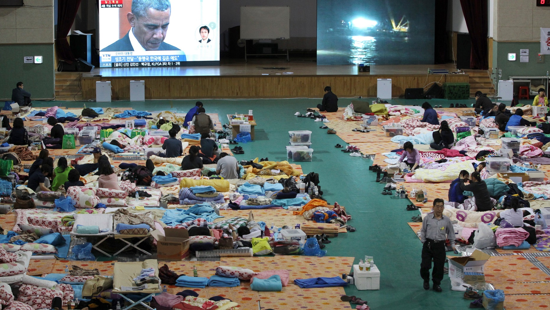 April 25, 2014 - A TV screen shows Pres. Obama paying silent tribute for the victims of South Korea's sunken ferry Sewol during a summit meeting with South Korean President Park Geun-hye as relatives of victims look on at a gymnasium in Jindo, South Korea. The South Korean government conceded that some bodies have been misidentified and announced changes to prevent such mistakes from happening again.