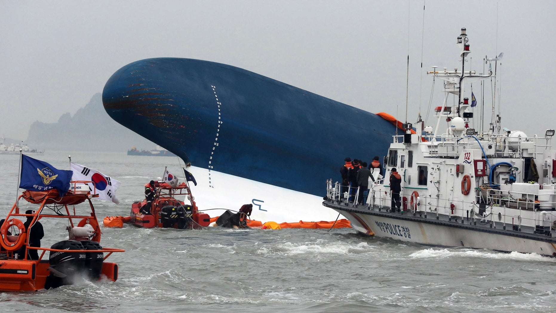 South Korean Coast Guard officers try to rescue missing passengers from a sunken ferry in the water off the southern coast near Jindo, south of Seoul, South Korea, Thursday, April 17, 2014.  Fears rose Thursday for the fate of more than 280 passengers still missing more than 24 hours after their ferry flipped onto its side and filled with water off the southern coast of South Korea. (AP Photo/Yonhap) KOREA OUT