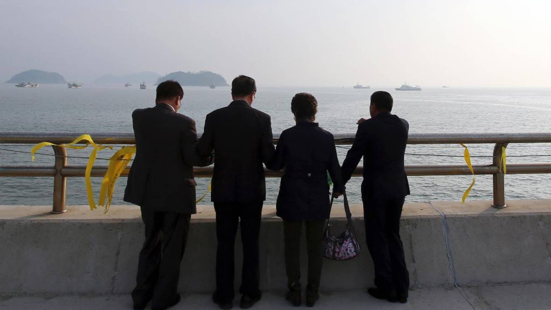 Christians pray near yellow ribbons with messages for the victims and missing passengers of the sunken ferry Sewol, at a port in Jindo, south of Seoul, South Korea, Monday, May 12, 2014. Bad weather prevented divers from searching inside the sunken, deteriorating South Korean ferry for a third day Monday. (AP Photo/Yonhap) KOREA OUT