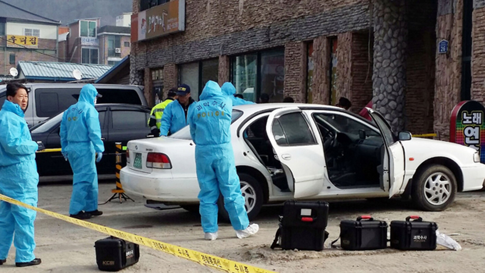 Feb. 25, 2015: South Korean police officers investigate a vehicle near the scene of an incident in Sejong, south of Seoul. South Korean police said Wednesday that three people were dead after a gunman opened fire at a store in Sejong City and set the store on fire before fleeing. (AP Photo/Yonhap, Lee Jae-lim)