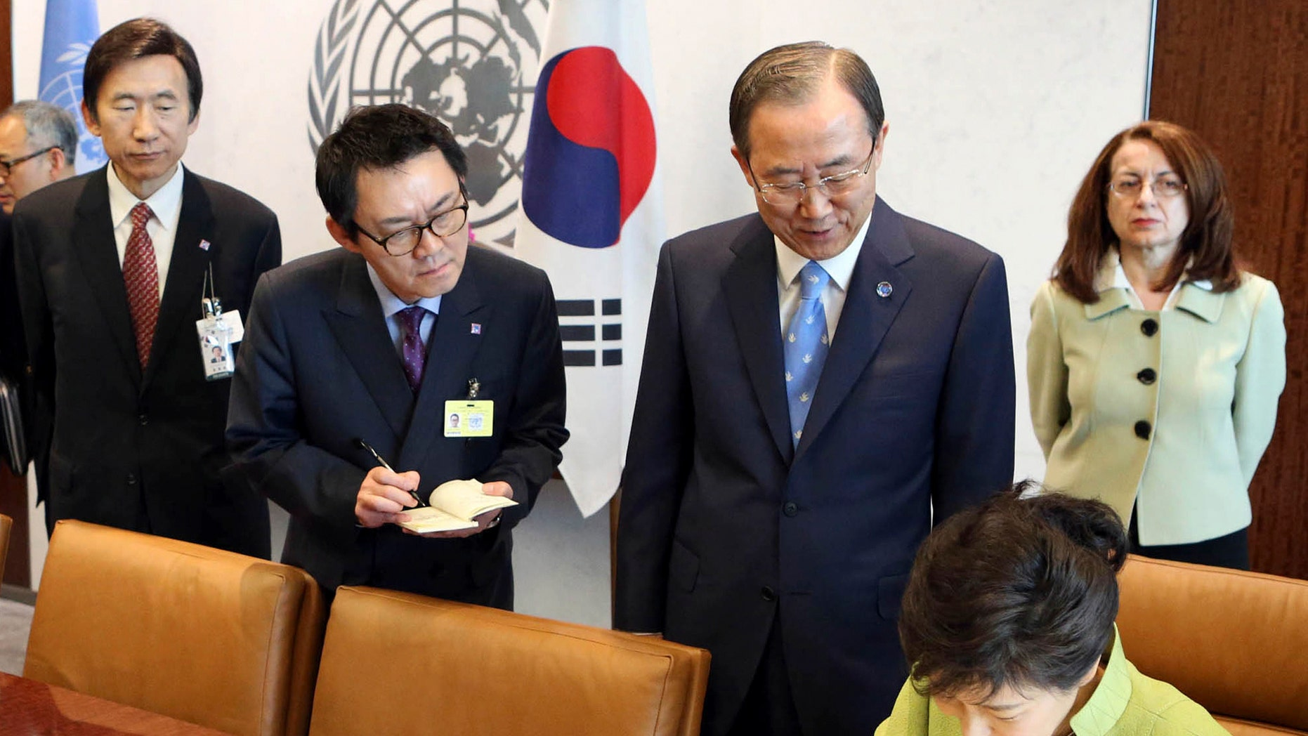 May 6, 2013: In this photo, South Korean President's spokesman Yoon Chang-jung, third right top, watches South Korean President Park Geun-hye, right bottom, sign the guestbook as UN Secretary General Ban Ki-moon, second right, looks on, at United Nations headquarters.