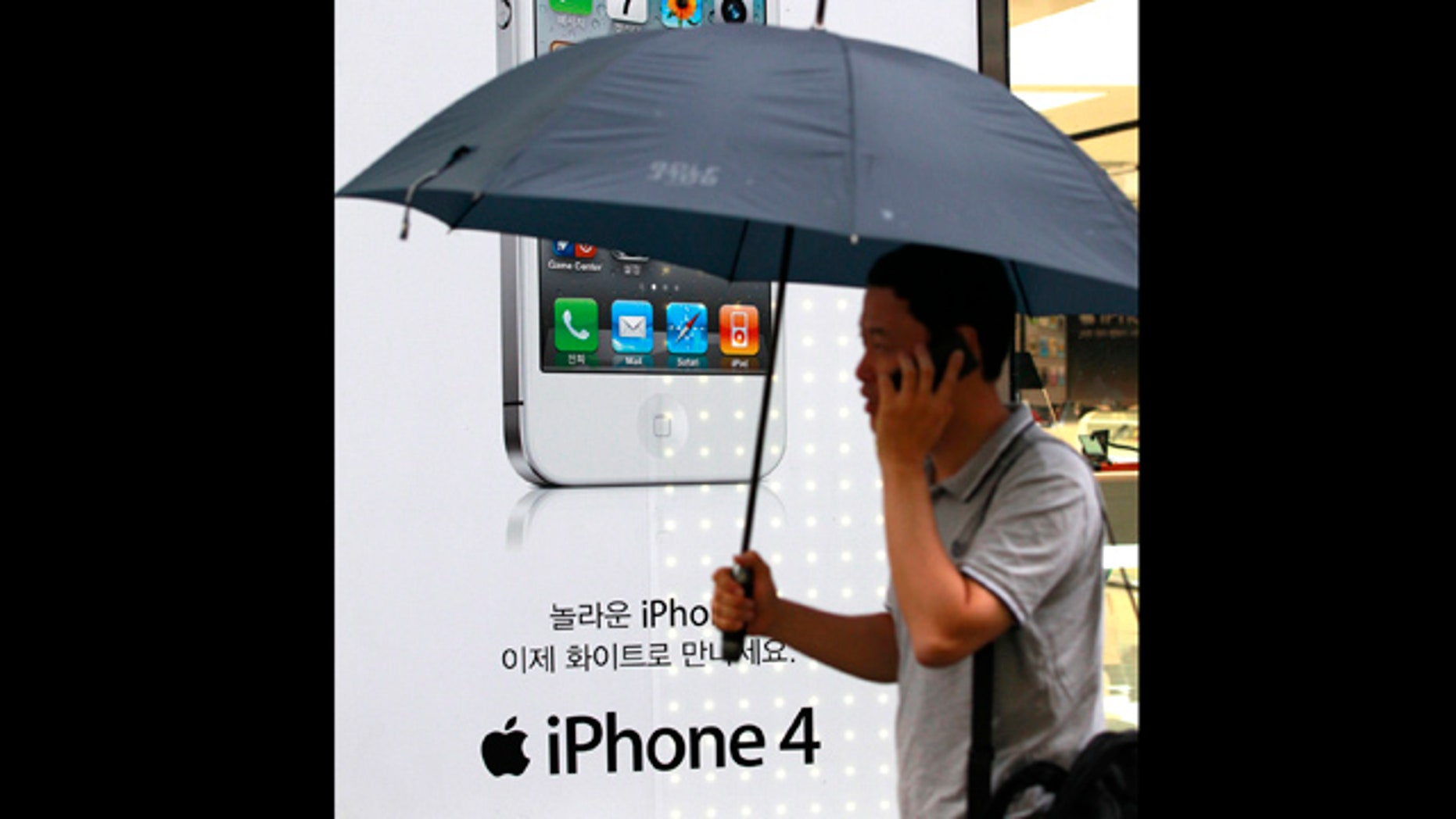 Aug. 17, 2011: A man passes by an Apple iPhone advertisement at downtown Seoul, South Korea. A group of nearly 27,000 South Koreans is suing Apple for $26 million for what they claim are privacy violations from the collection of iPhone user location information.